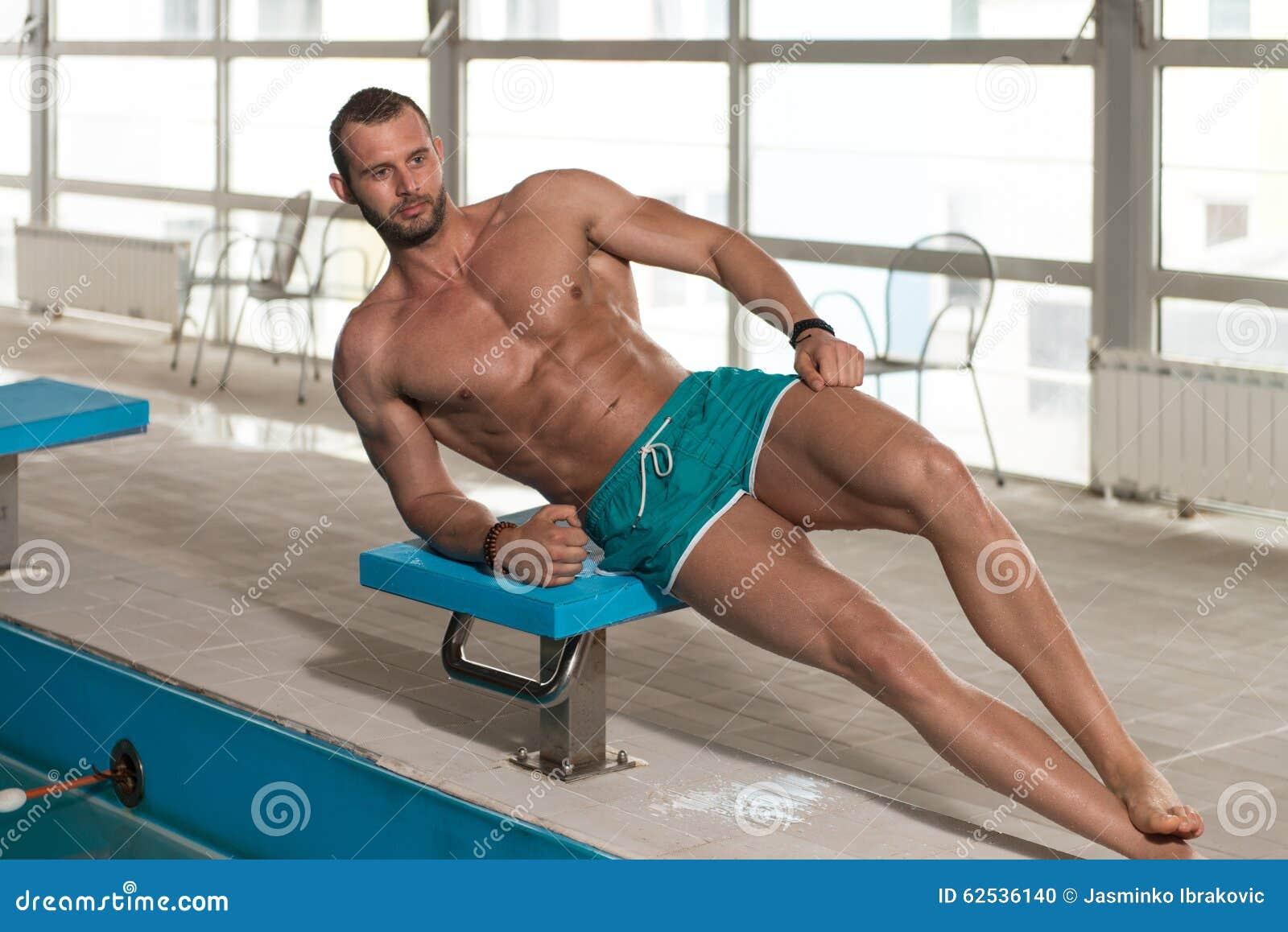 看强壮男子的人的年轻人旅馆室内游泳池