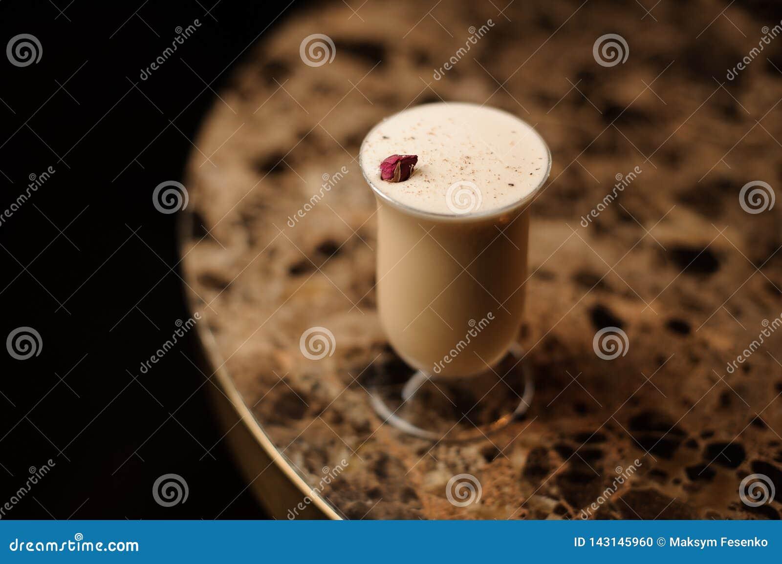 看法从上面在用在桌上的一个一红色玫瑰色芽身分装饰的玻璃的可口鸡尾酒
