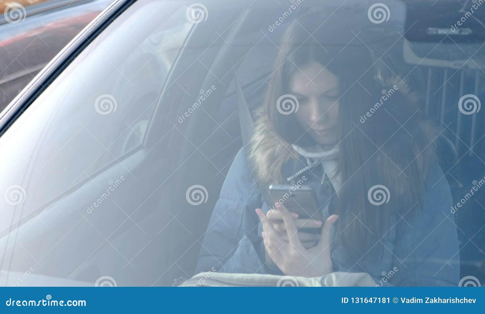 看法通过汽车的挡风玻璃在年轻深色的妇女的看电话的蓝色下来夹克的