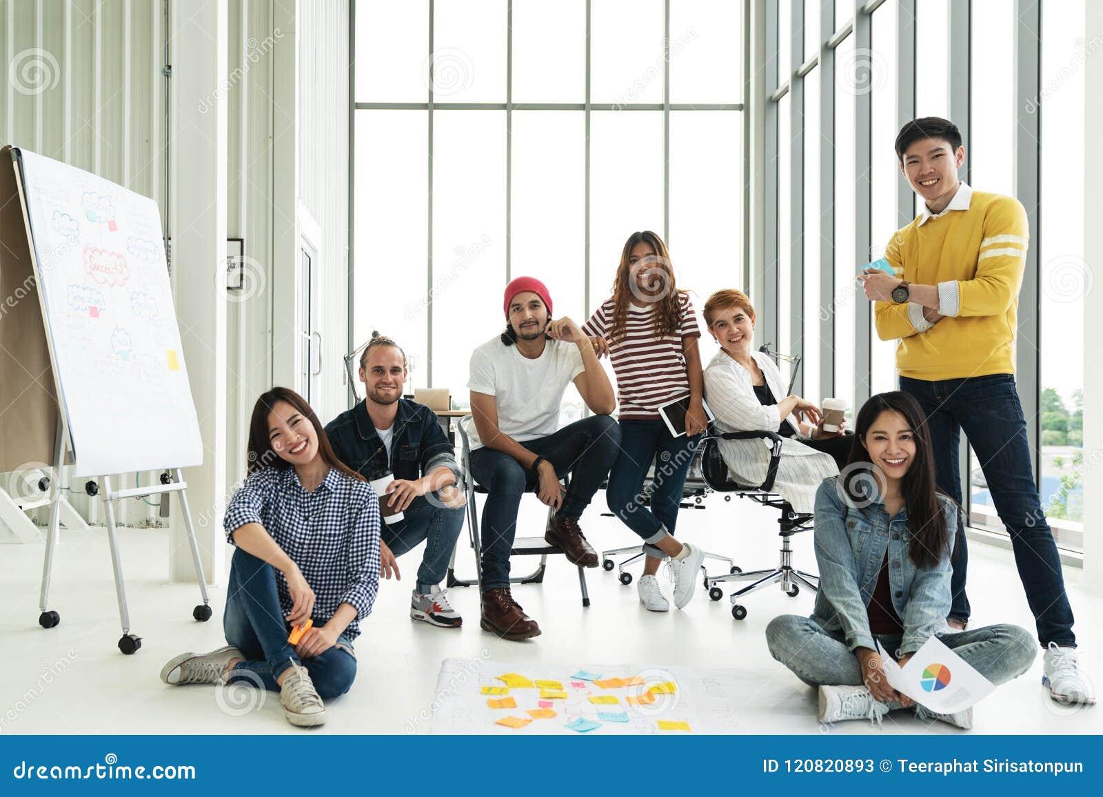看照相机和微笑的愉快的不同的创造性的企业队小组画象