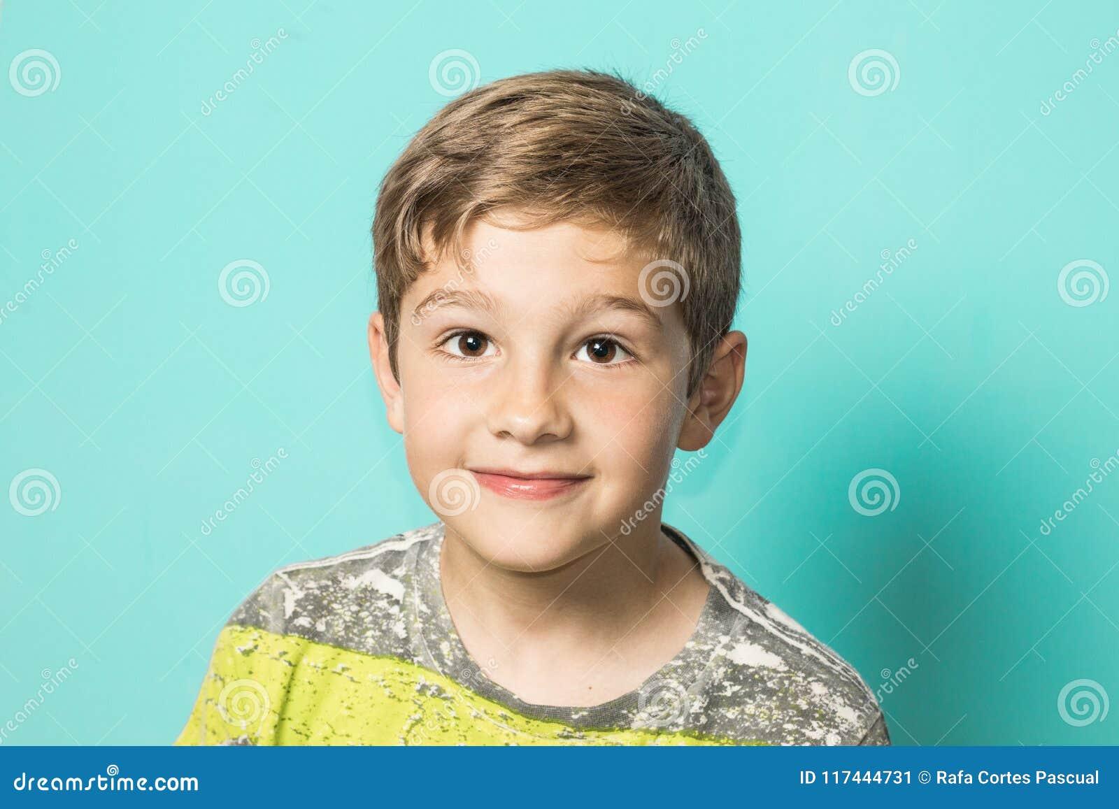 看照相机和微笑的白肤金发的孩子 有表示的孩子在愉快的面孔