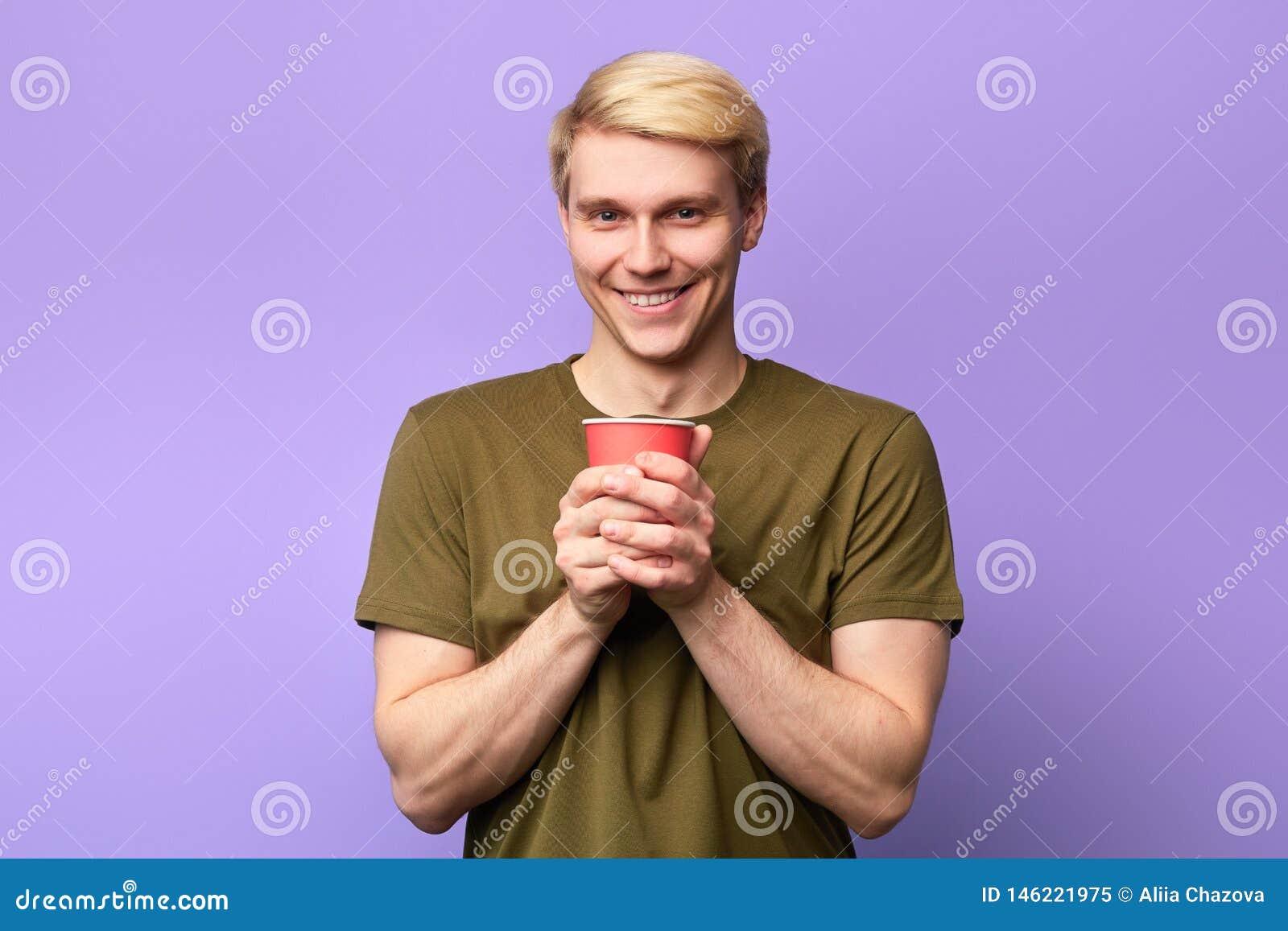 看照相机和拿着塑料杯子的正面愉快的年轻帅哥