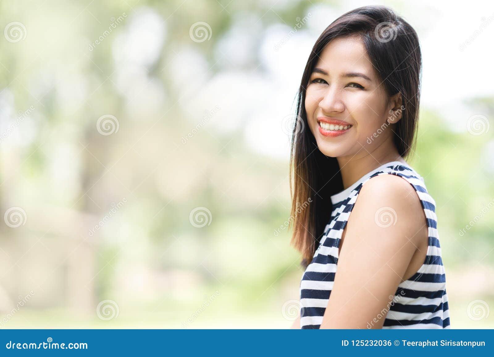 看照相机的年轻可爱的亚裔妇女画象微笑与确信和正面生活方式概念在室外公园