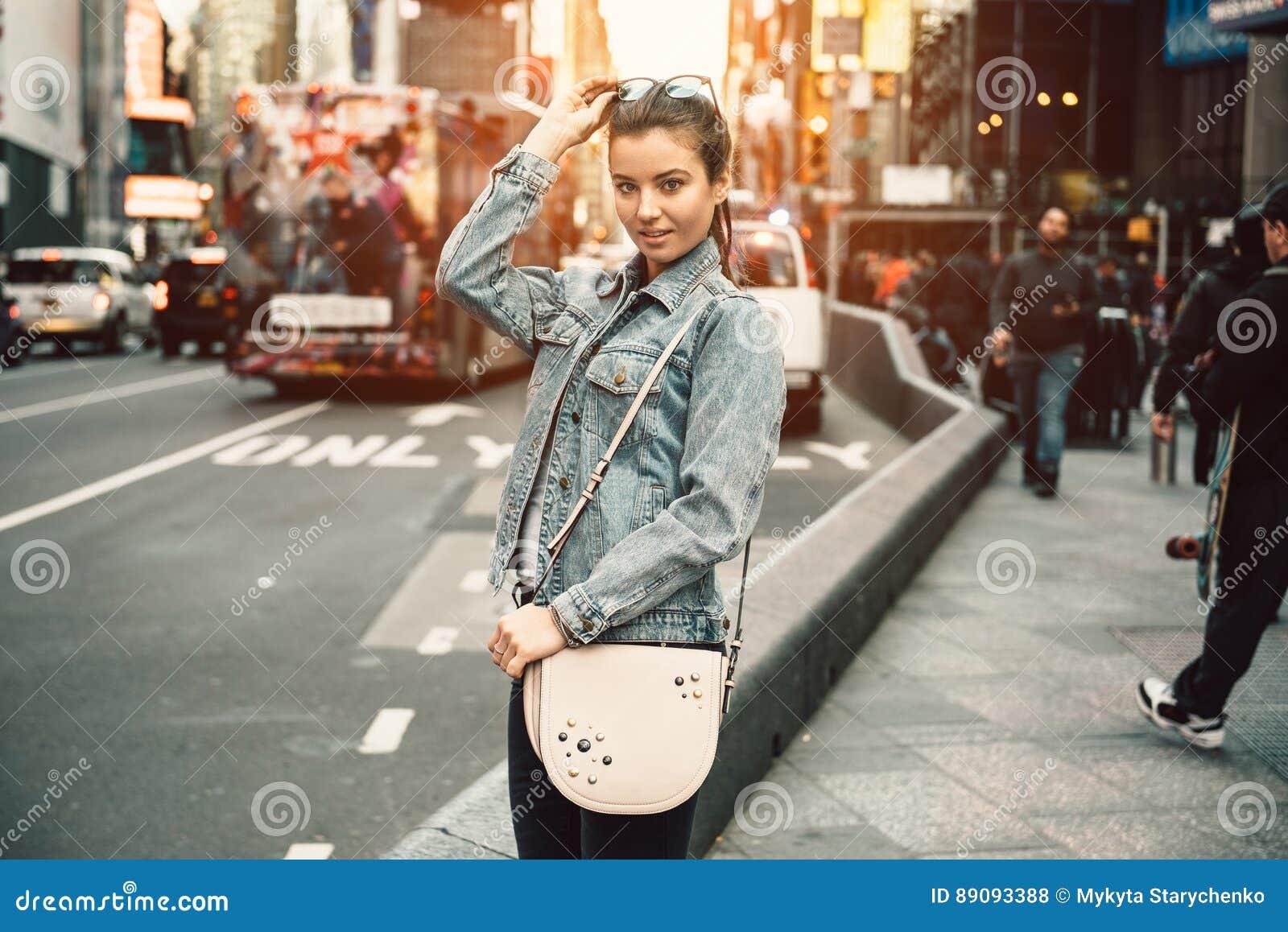 看照相机的愉快的年轻旅游妇女生活方式照片拿着袋子钱包和太阳镜在晴朗的繁忙的城市街道上