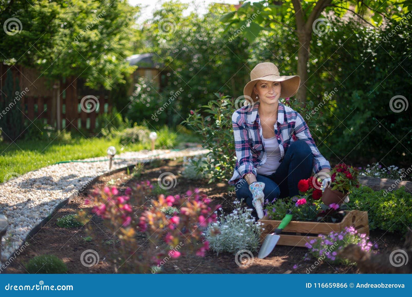 看照相机的美丽的女性花匠微笑和拿着木板箱有很多花