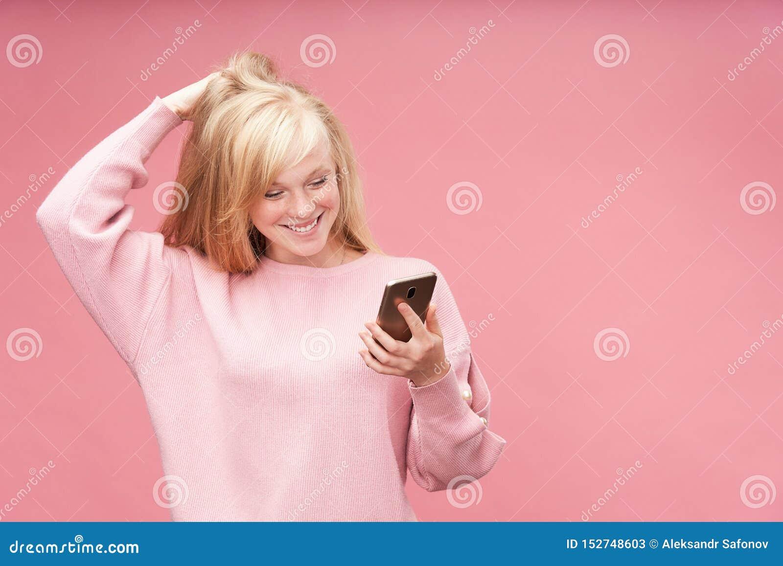 看电话的情感女孩 年轻美丽的金发碧眼的女人看赞赏握他的手的智能手机对他的头 ??
