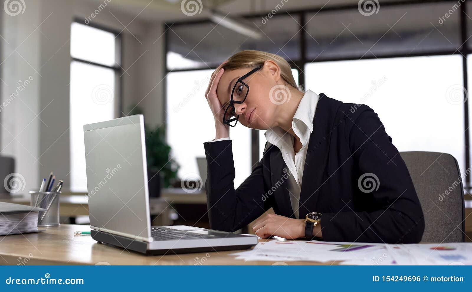 看膝上型计算机的哀伤的妇女,担心困难的项目,缺乏经验