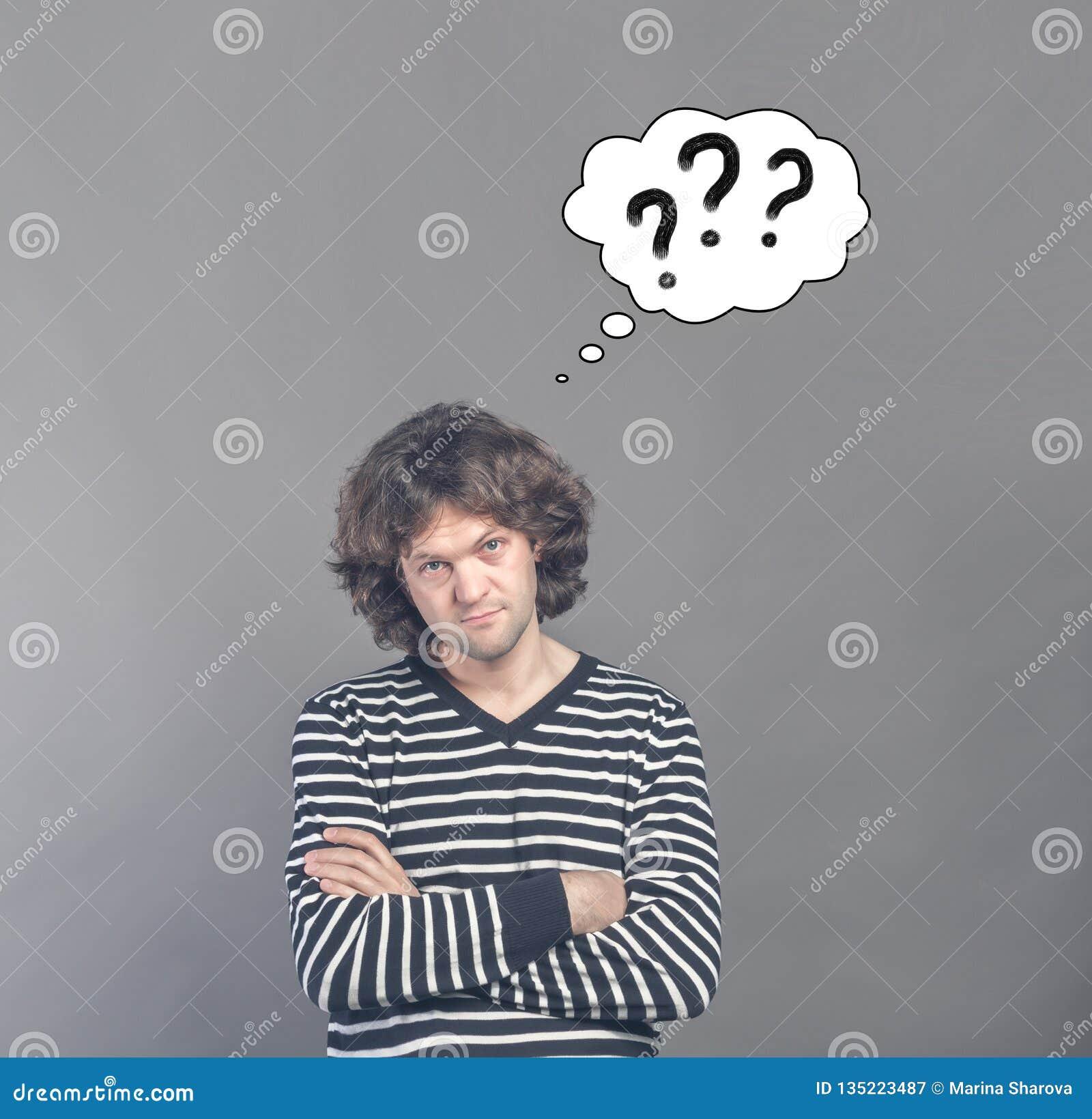 看起来怀疑的人可疑和可疑与想法拉长的云彩与三个问号的在它 某一不赞成