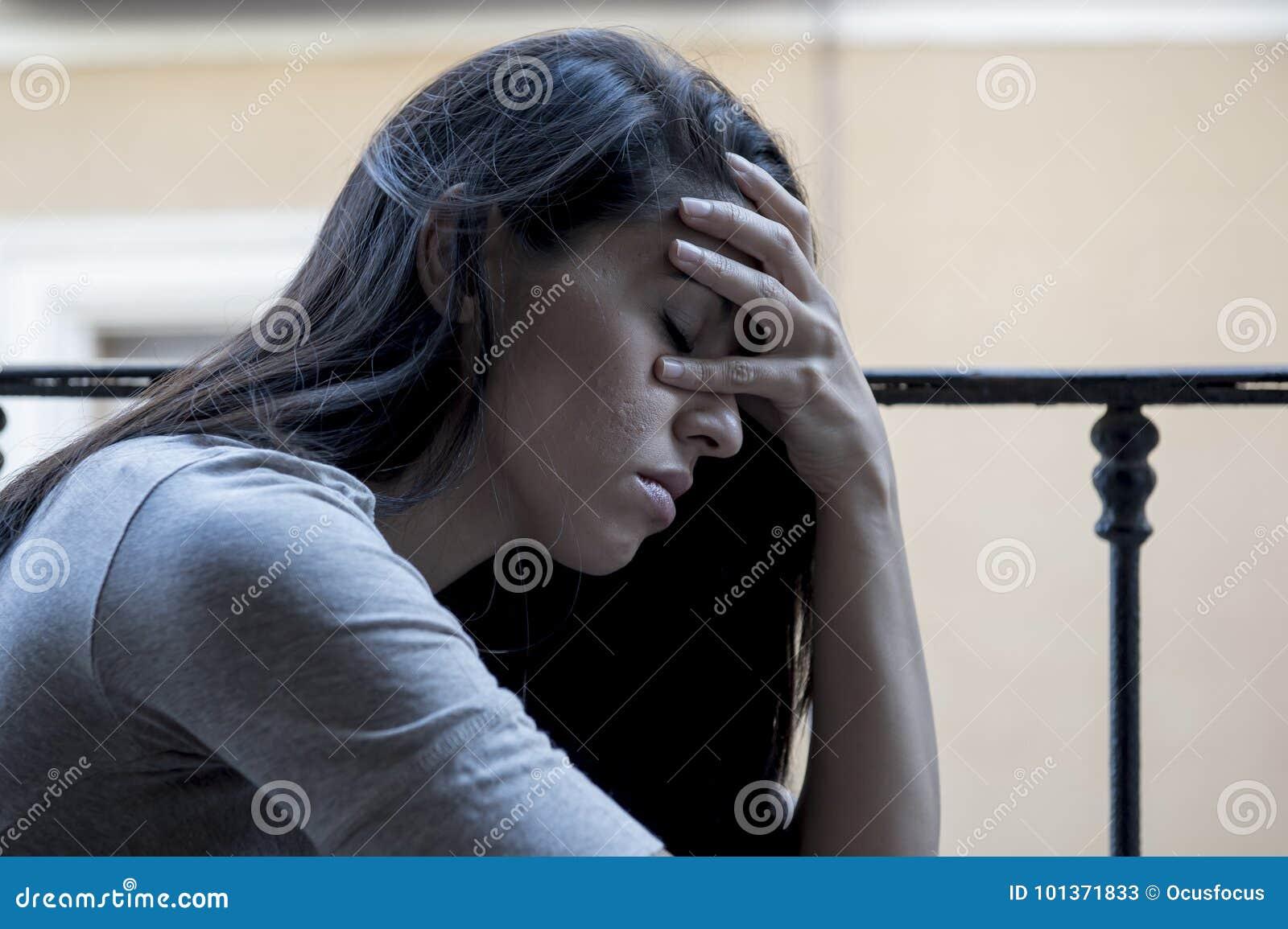 看起来绝望哀伤的拉丁妇女在家的阳台被摧残的和沮丧的遭受的消沉