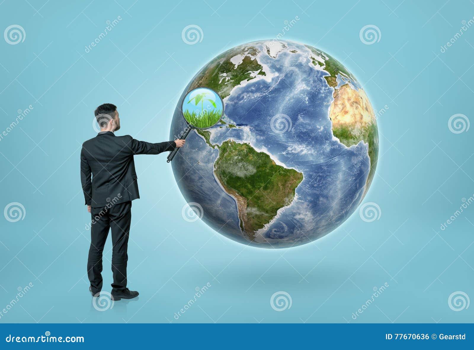 看通过地球上的放大镜和看见草的商人