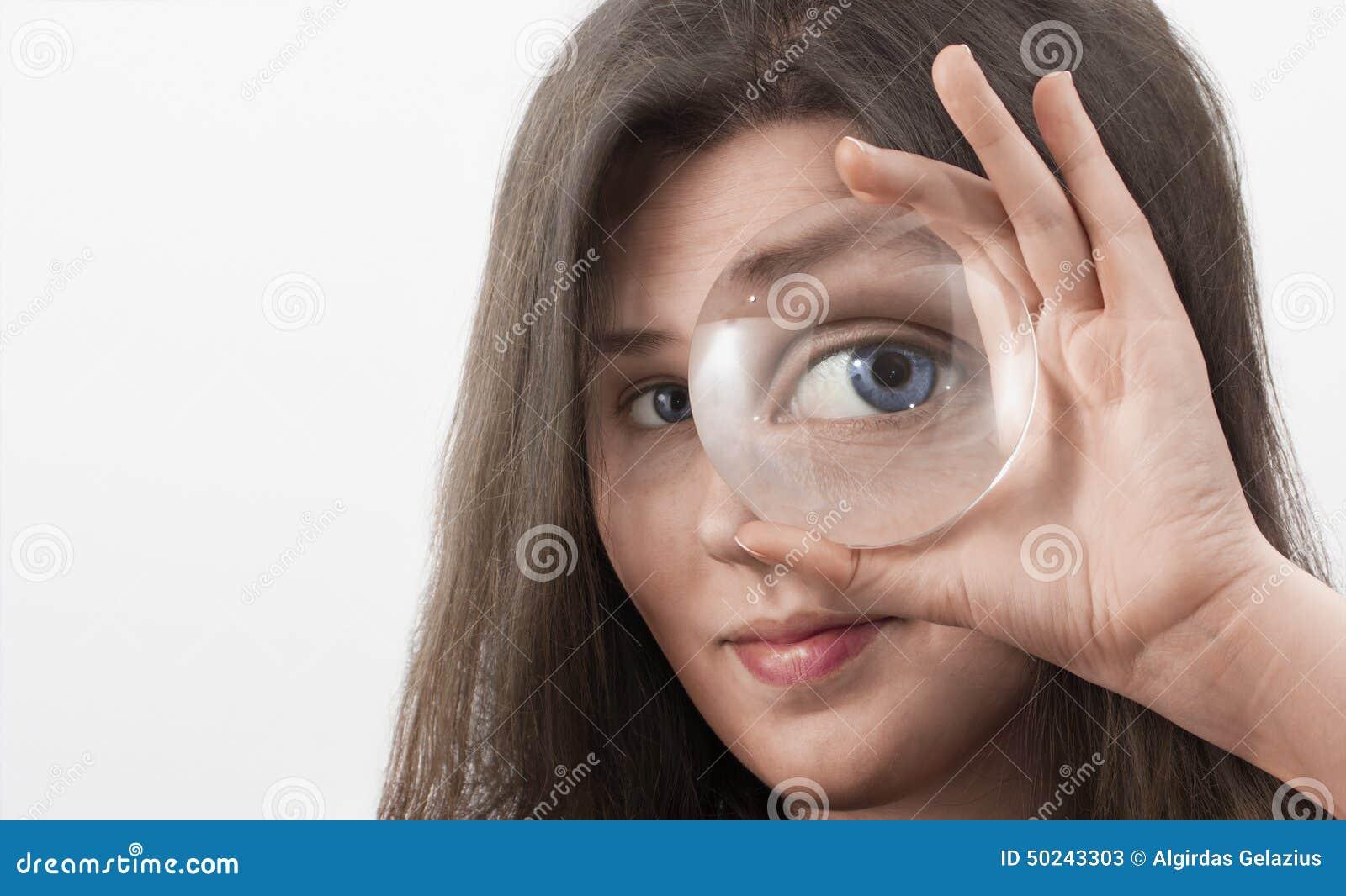 查寻通过放大镜关闭的女性蓝眼睛.
