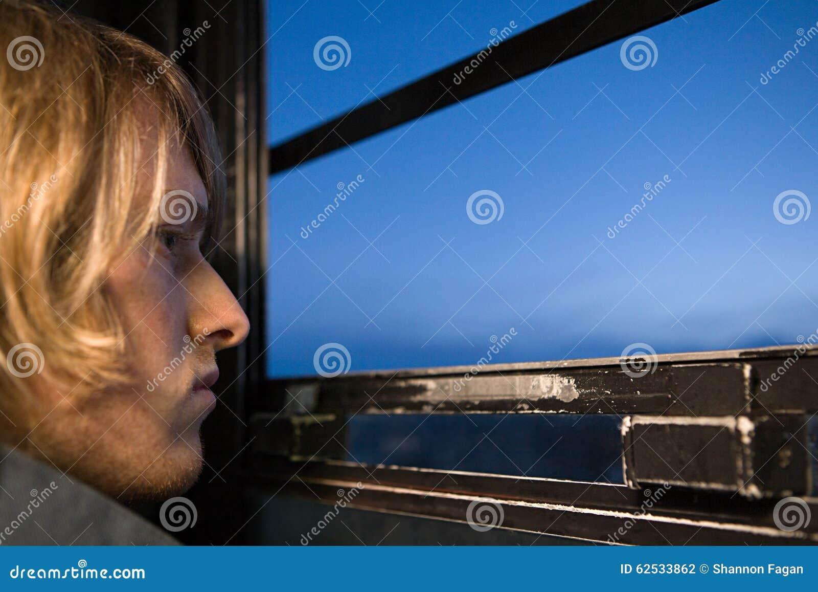 看通过窗口的年轻人