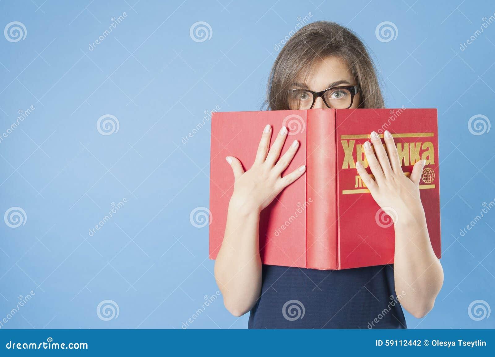 戴眼镜的女孩偷看从一本大书的后面