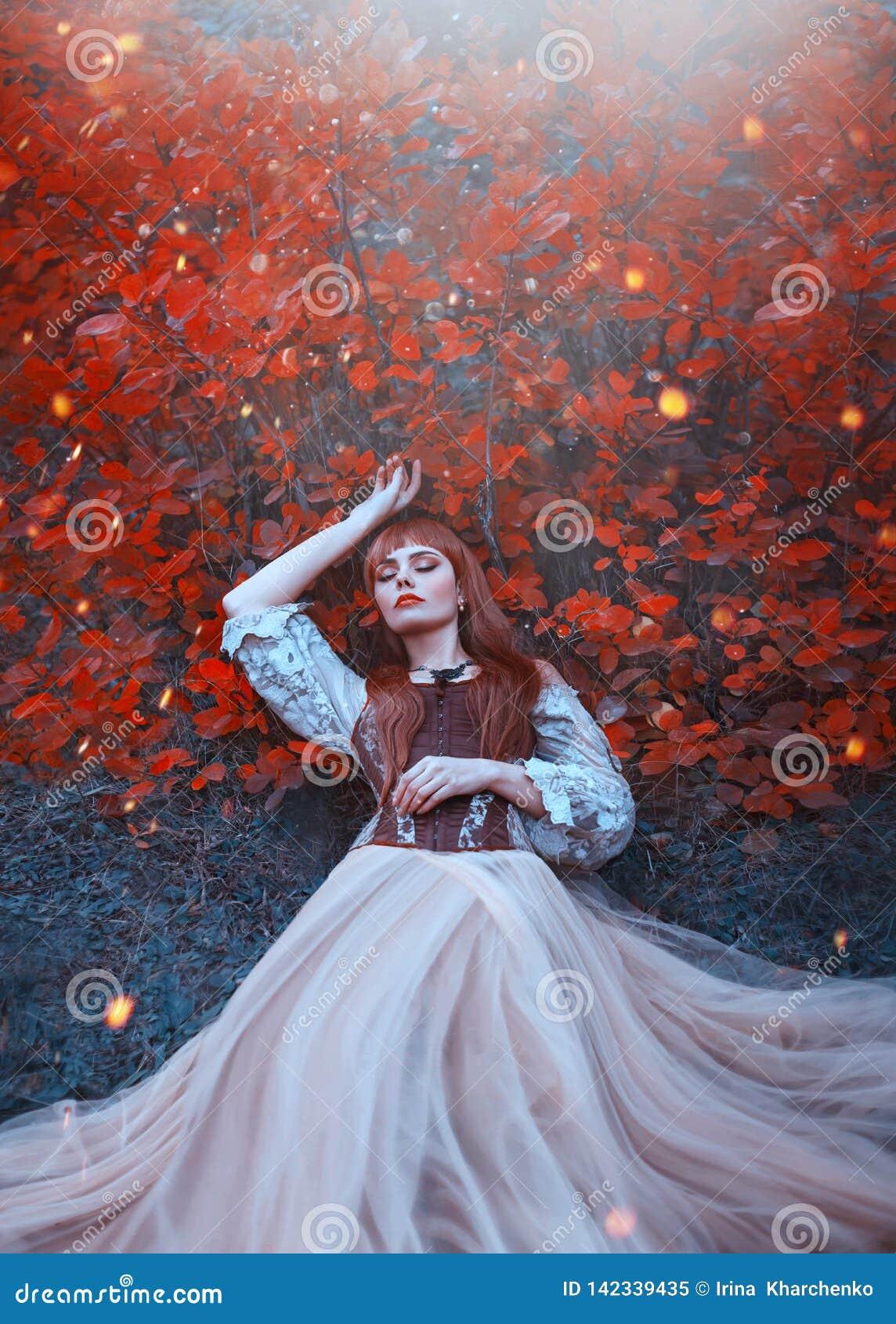 睡美人温暖的艺术照片,有火红的头发谎言的女孩在地面在橙色叶子下的密集的森林里在明亮