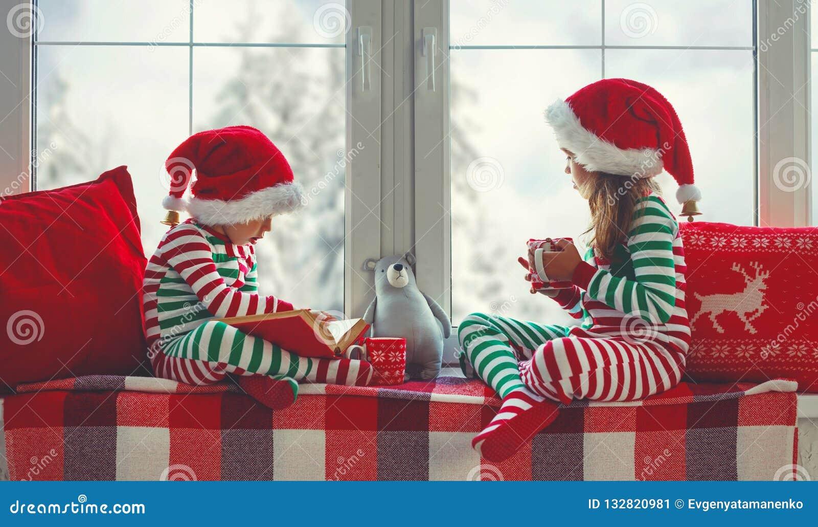 睡衣的孩子女孩和男孩是哀伤的在圣诞节早晨由窗口
