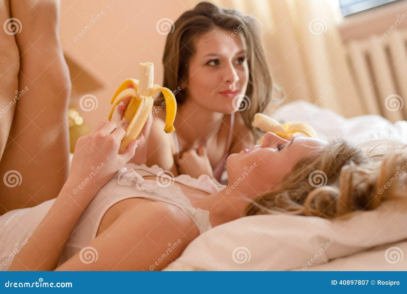 睡衣的2个美丽的少妇性感的女朋友吃香蕉的有乐趣放松的说谎在床图片