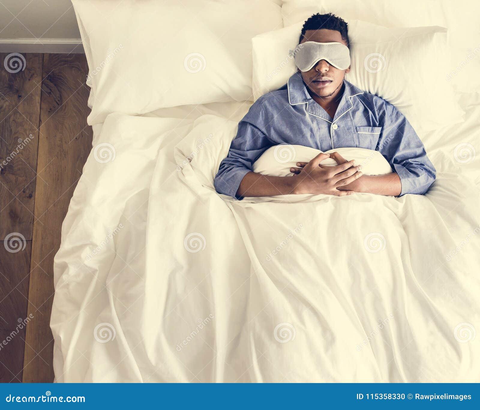 睡觉在与眼罩的床上的黑人
