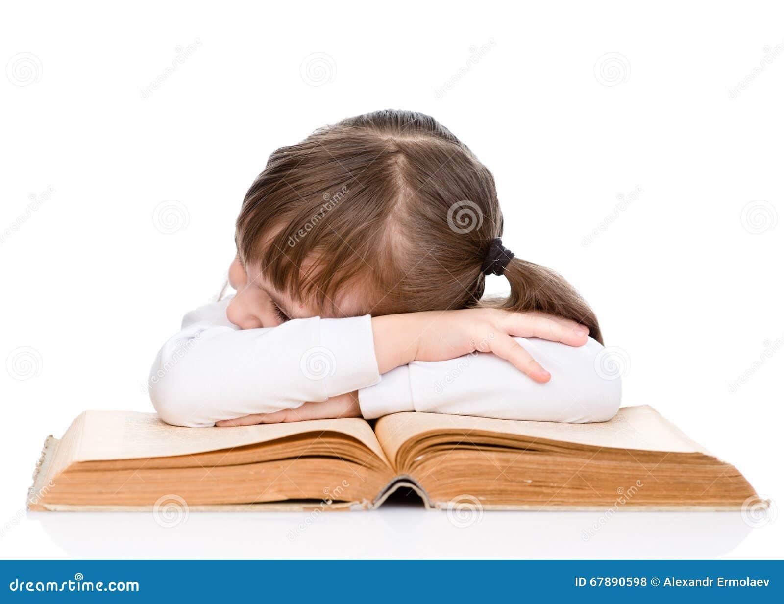 睡觉在书的疲乏的小女孩 查出在白色