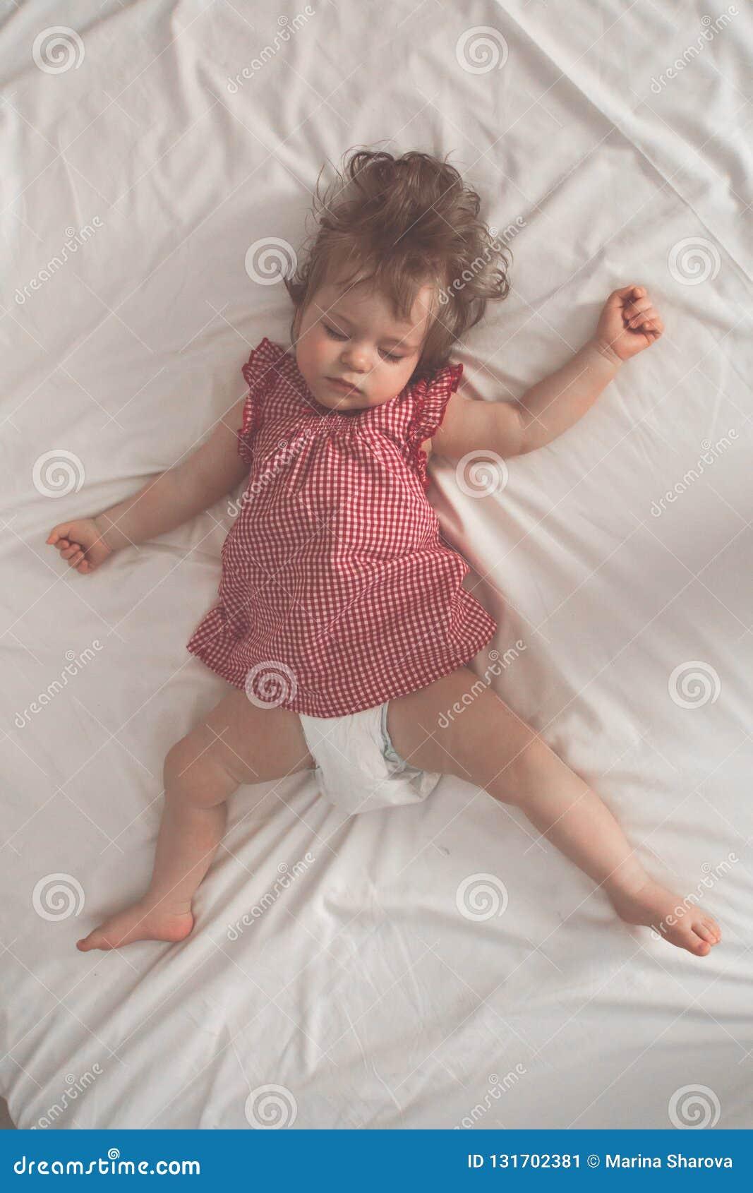 睡觉在后面的女婴有开放胳膊的和没有安慰者在一张床上与白色板料 平安睡觉在明亮