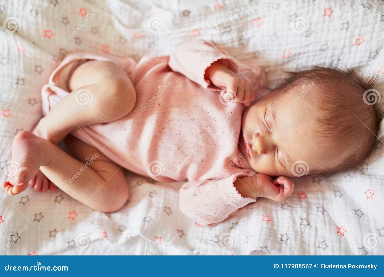 睡觉在她的小儿床的新出生的女婴