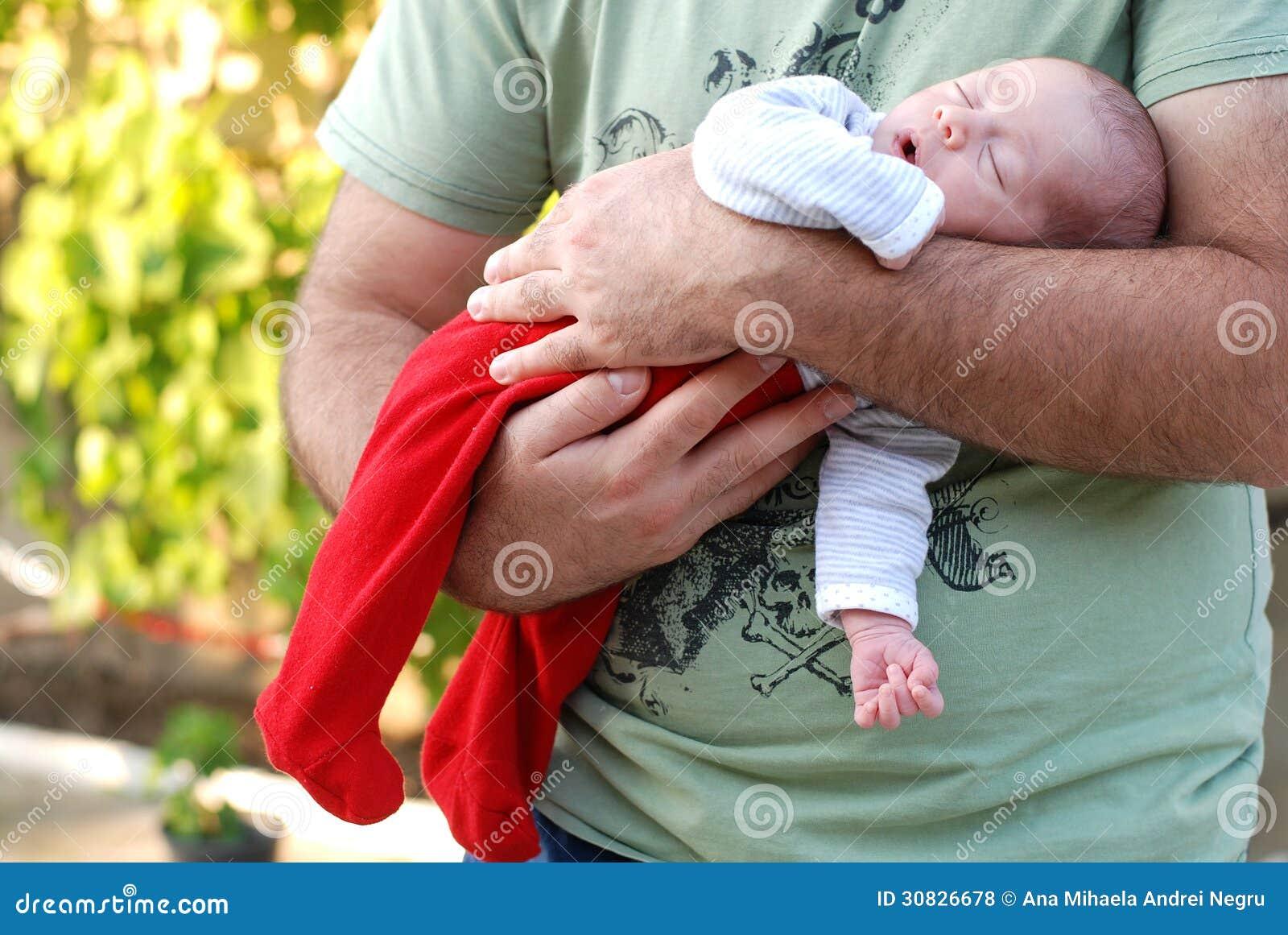 睡觉在她的父亲的新出生的女婴武装