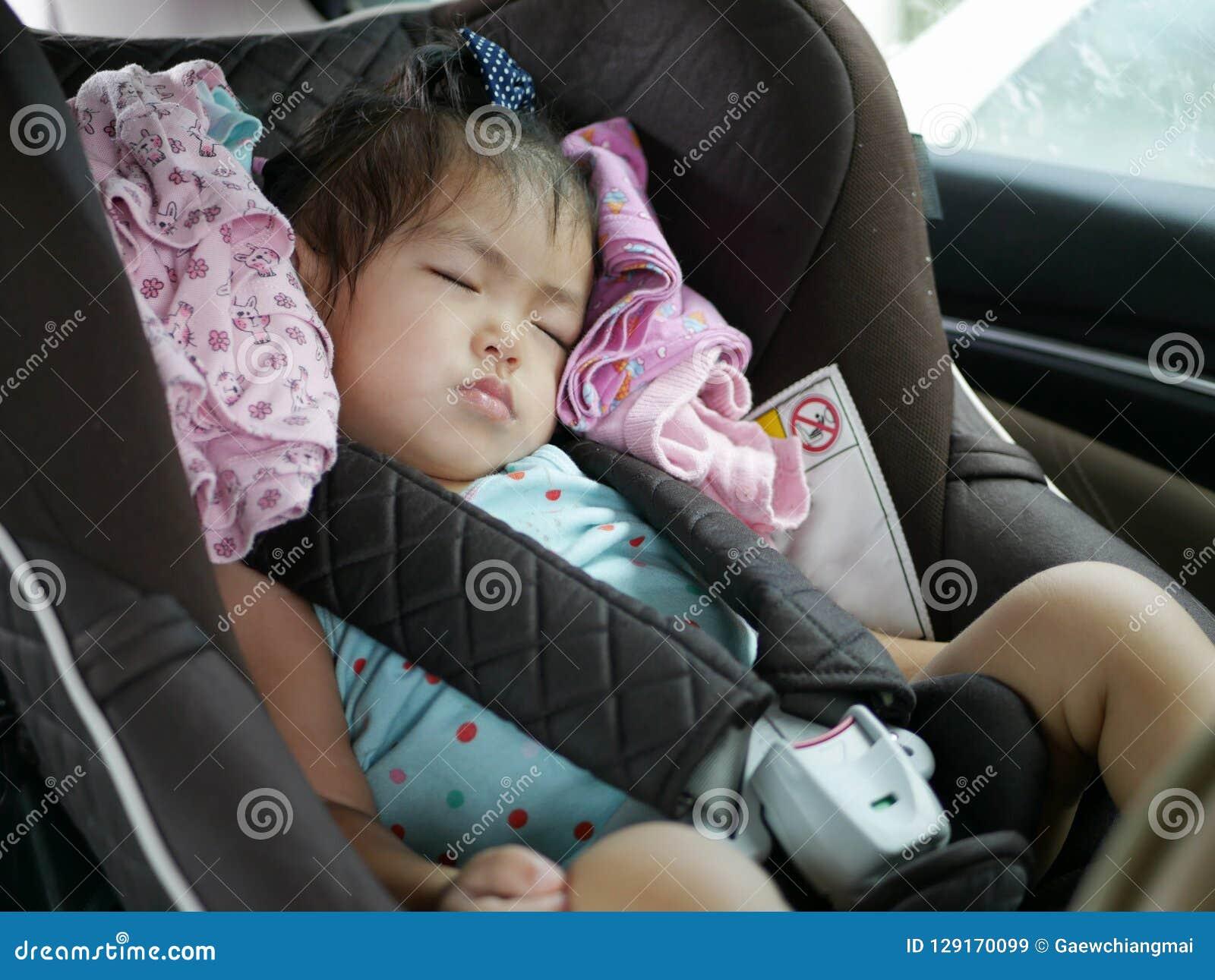 睡觉在婴孩安全的一个汽车座位的小亚裔女婴