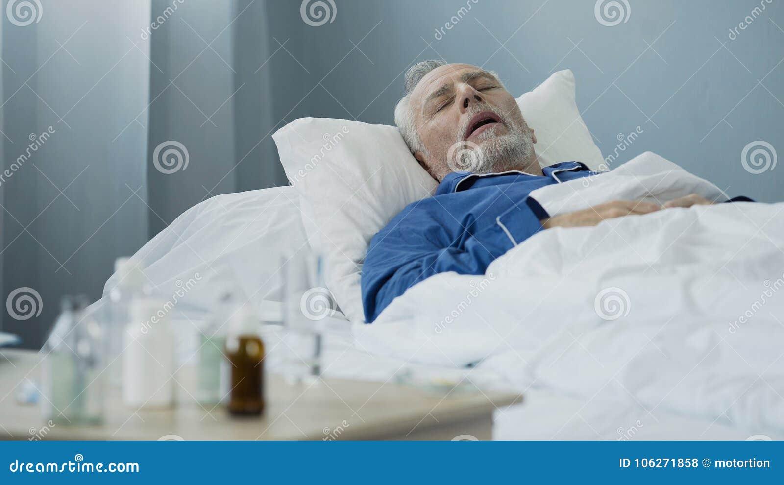 睡觉在床上的老人在医院病房,站立在桌上的抗生素