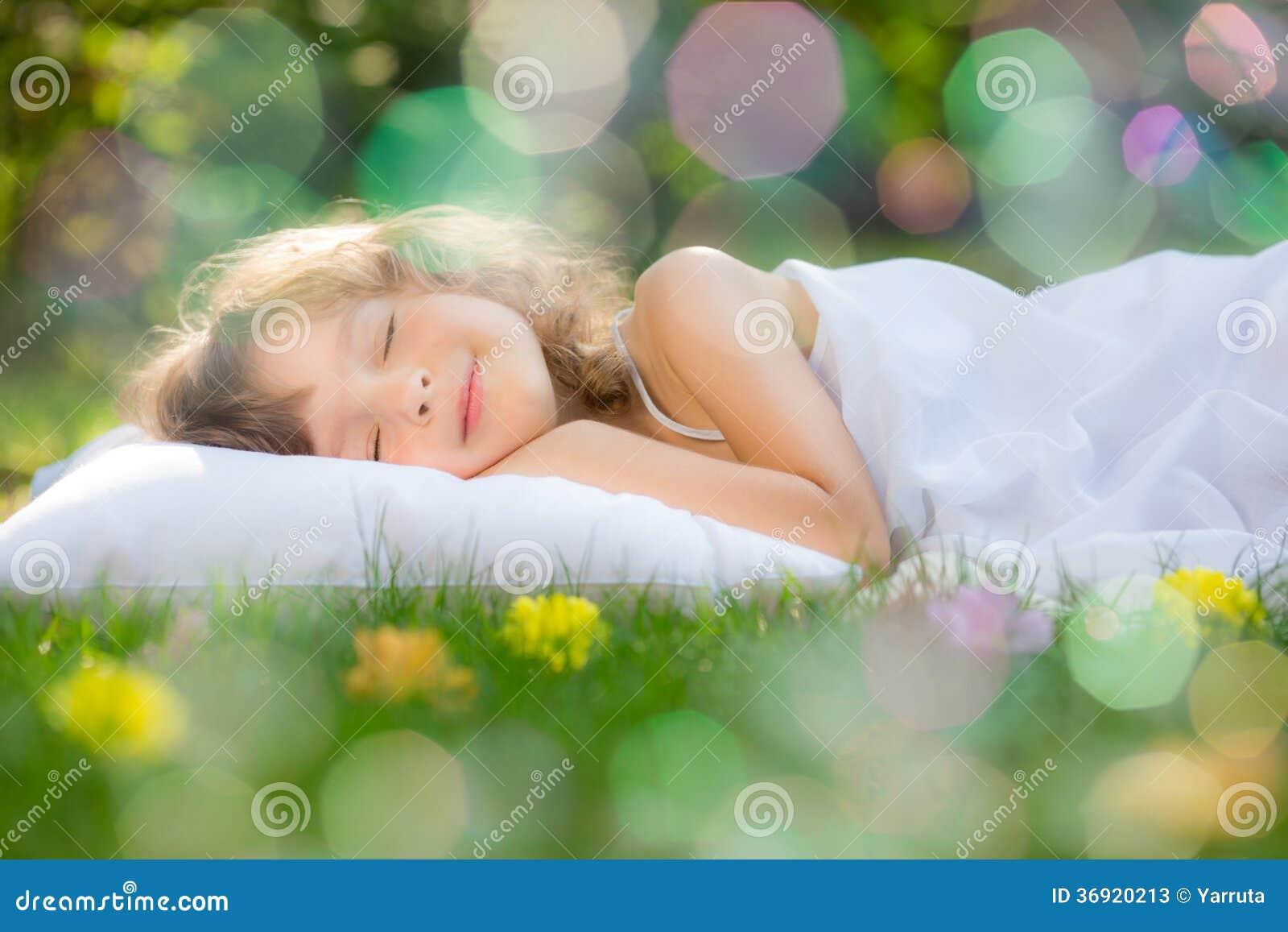 睡觉在春天庭院里的孩子