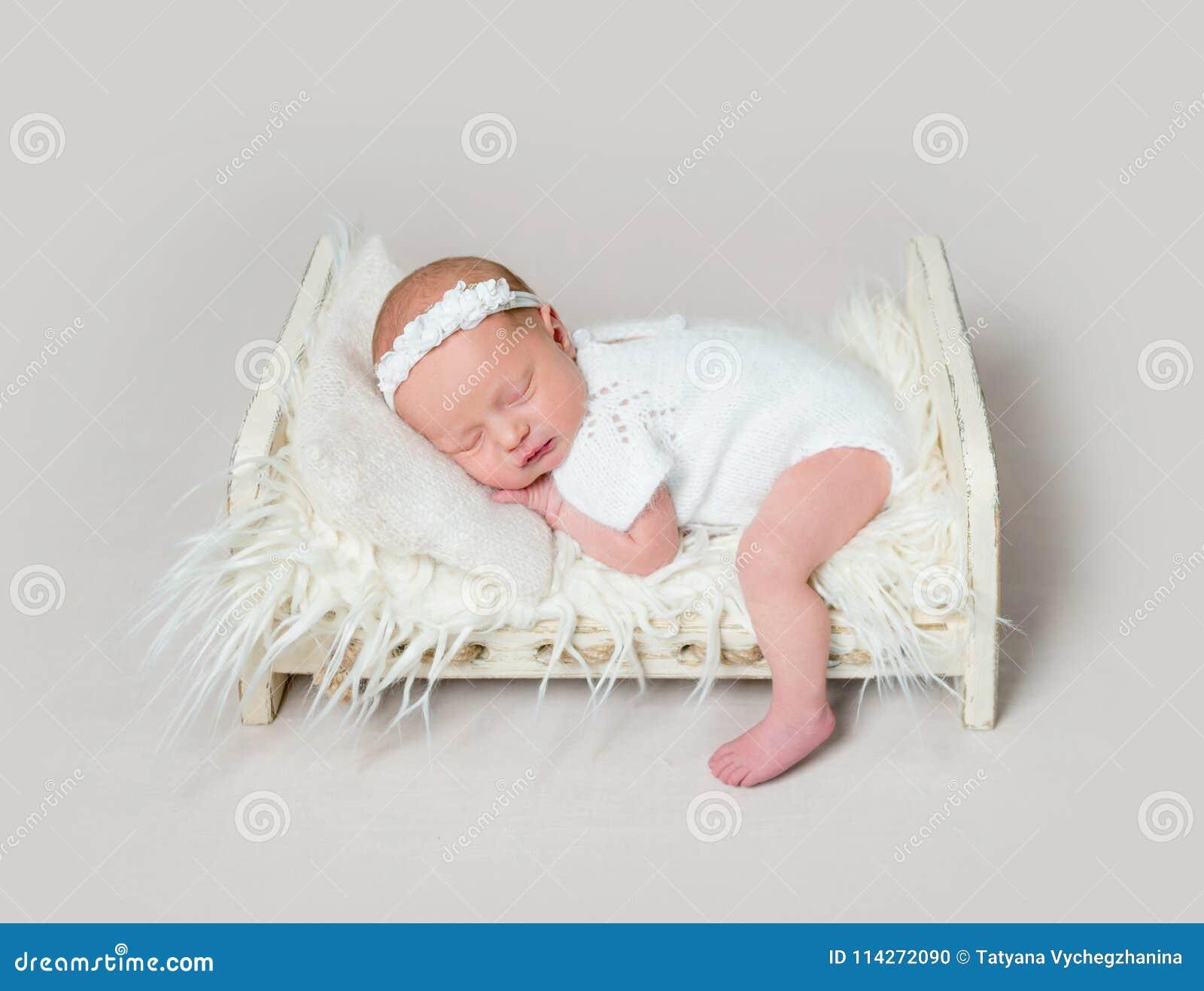 睡觉在有腿的小儿床的可爱的新出生的婴孩在地板上
