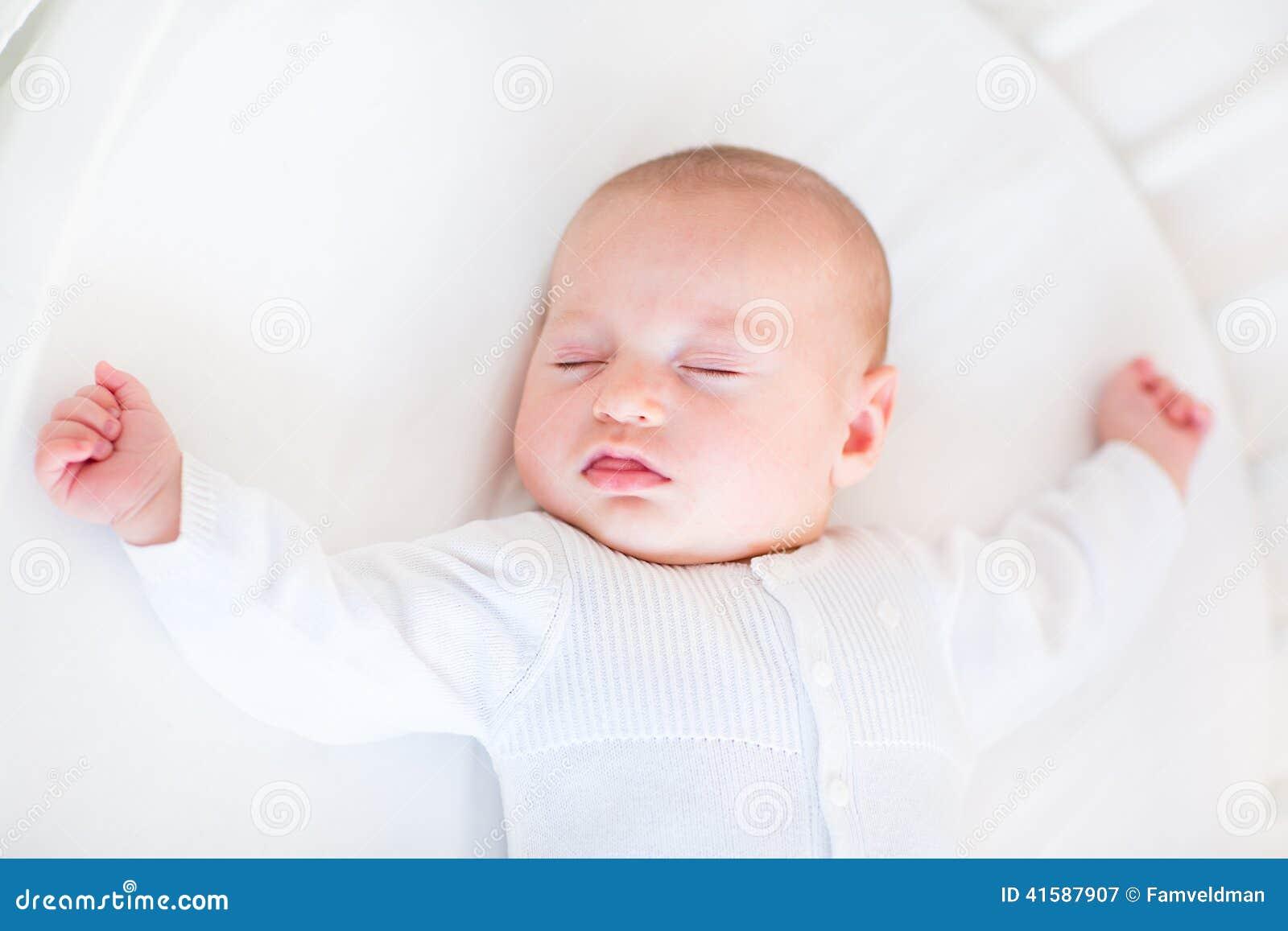 睡觉在白色圆的小儿床的小新出生的男婴