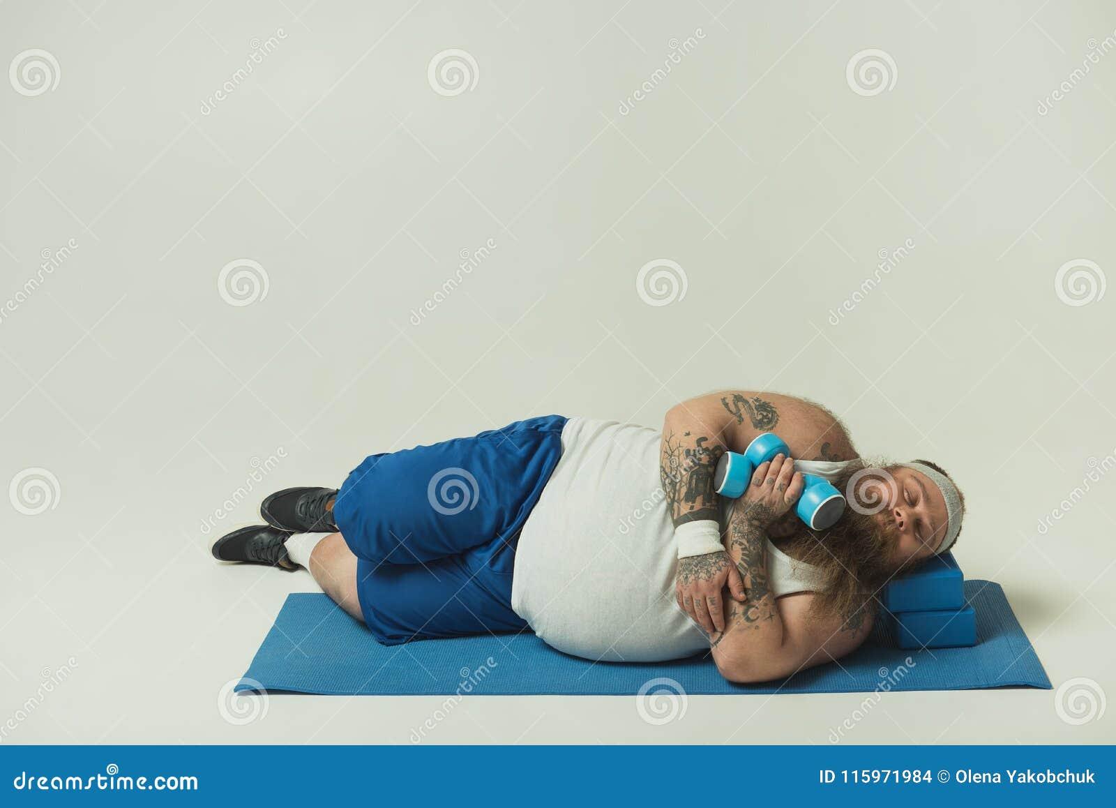 睡觉在训练以后的疲乏的肥胖人