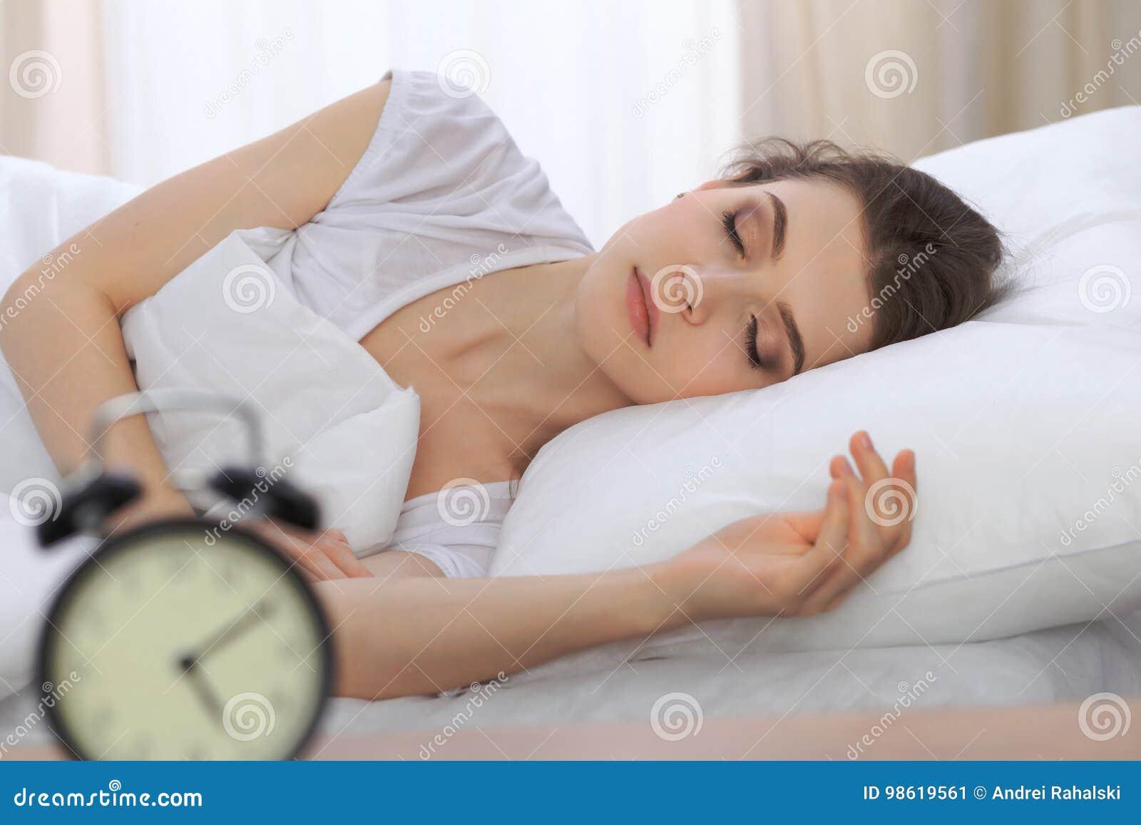 睡觉美丽的少妇,当在她的床上和舒适地时放松 为工作醒或是容易的