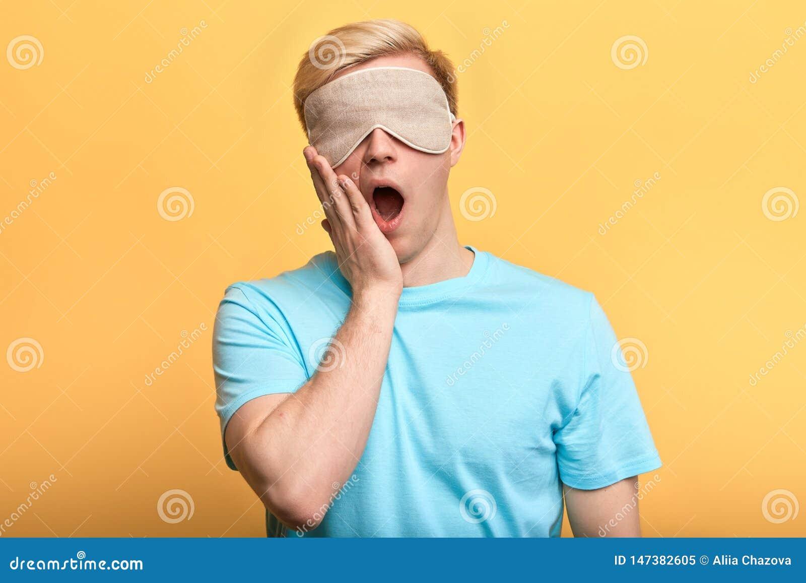 睡觉面具的年轻人与在打呵欠他的嘴的plam