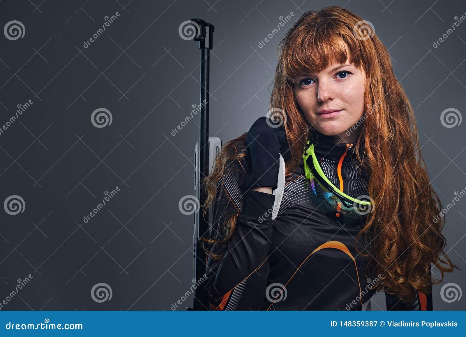瞄准与一杆竞争枪的红头发人女性两项竞赛冠军
