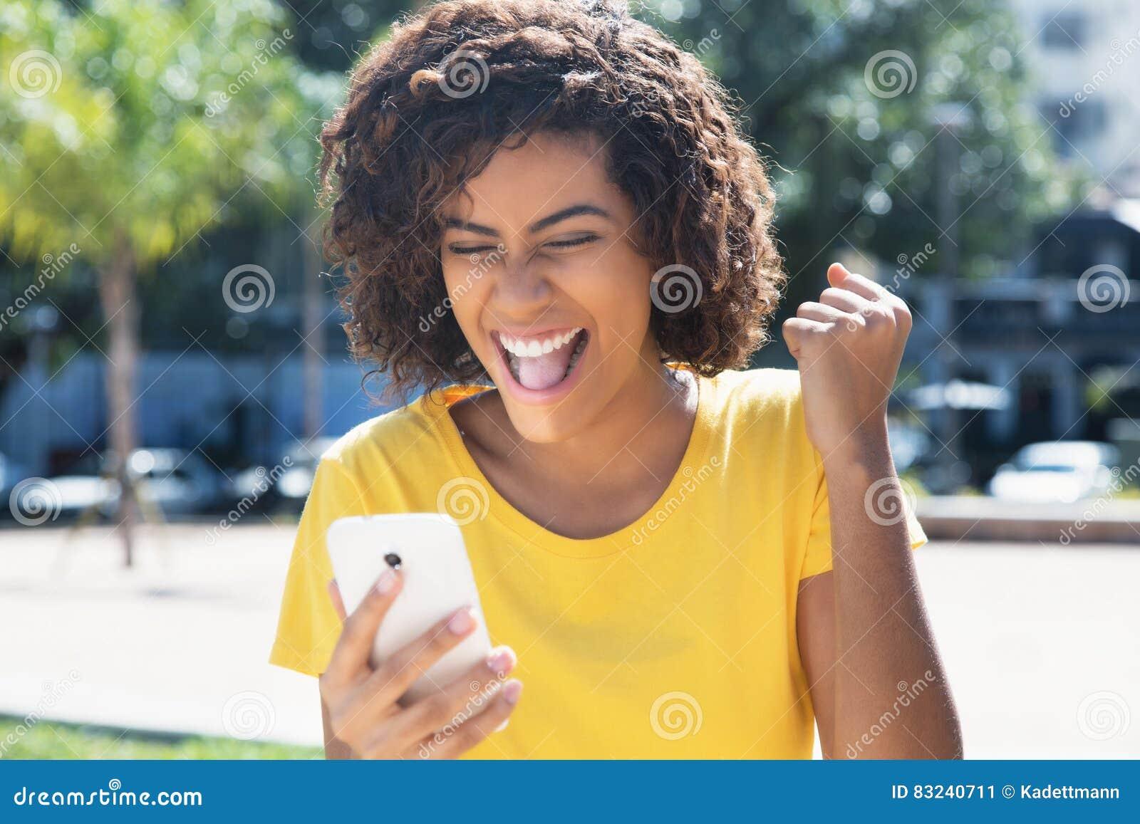 知道好消息的年轻拉丁妇女由电话