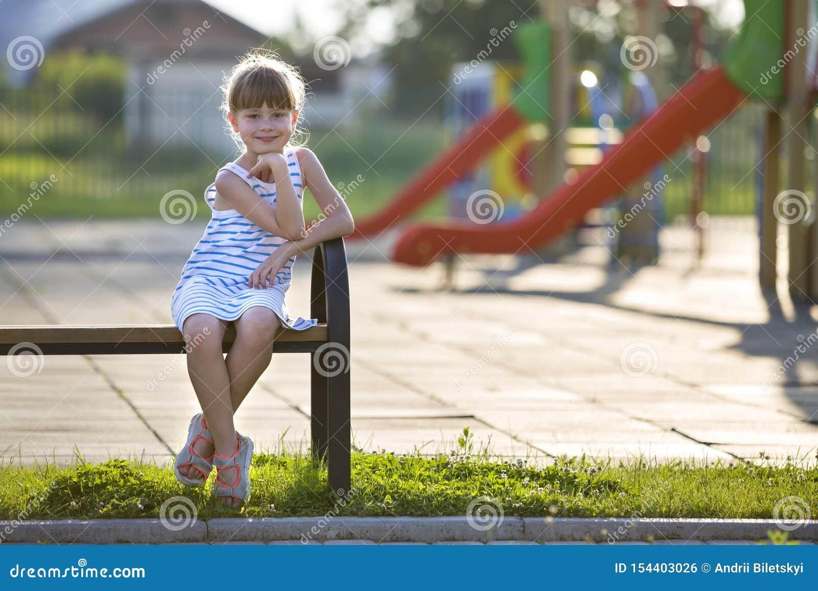 短的礼服的逗人喜爱的少女单独户外坐操场长凳在晴朗的夏日