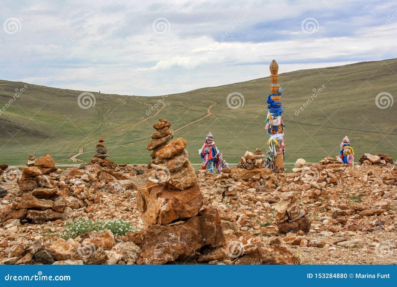 石头金字塔和一根宗教柱子栓与五颜六色的丝带