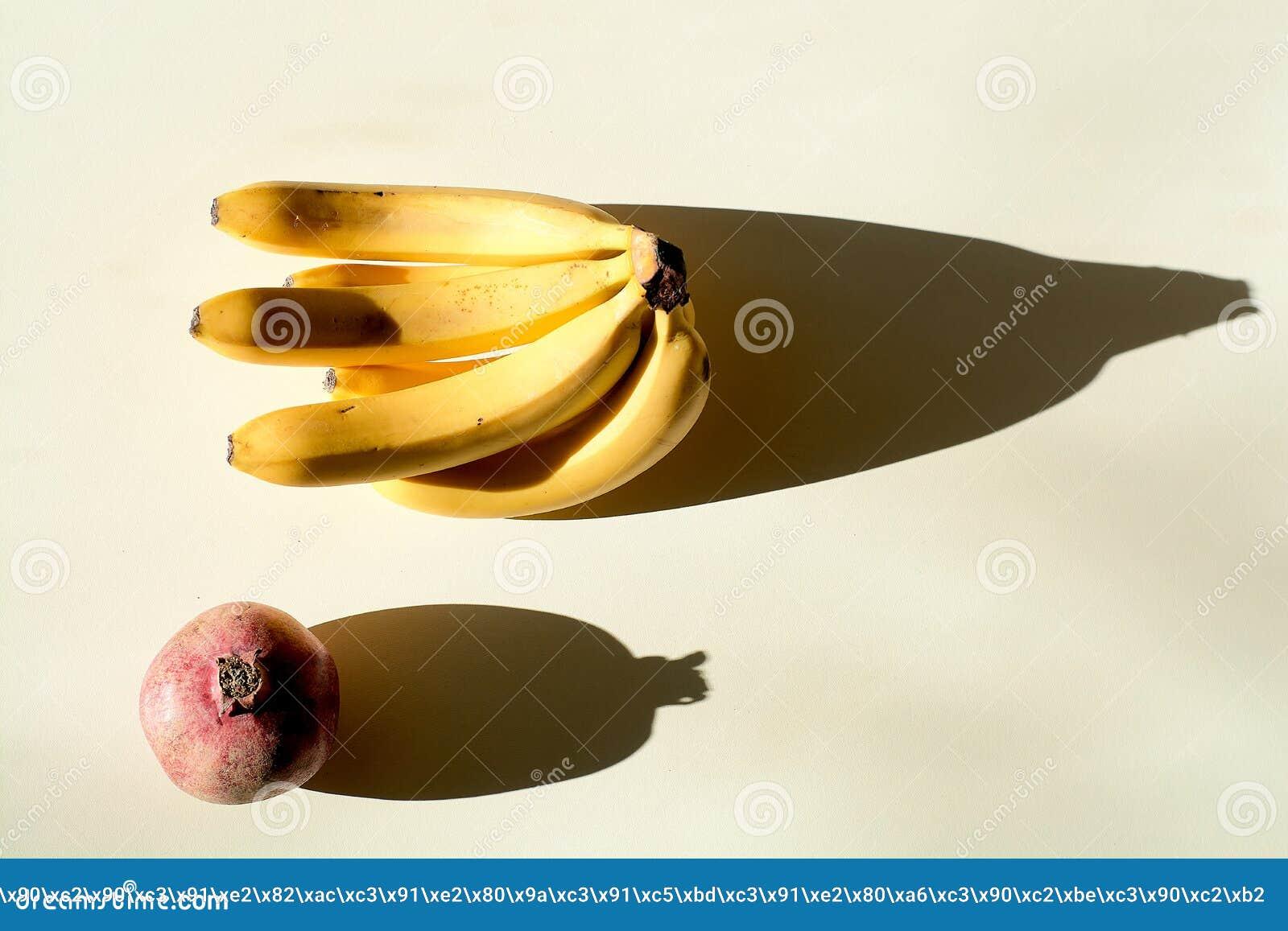 石榴和一束香蕉 成熟红色水多的石榴和成熟束香蕉