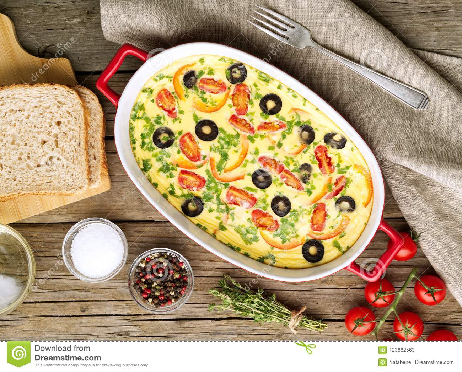 砂锅盘,可口热的煎蛋卷用蕃茄,橄榄,辣椒的果实 老木纹理背景,顶视图