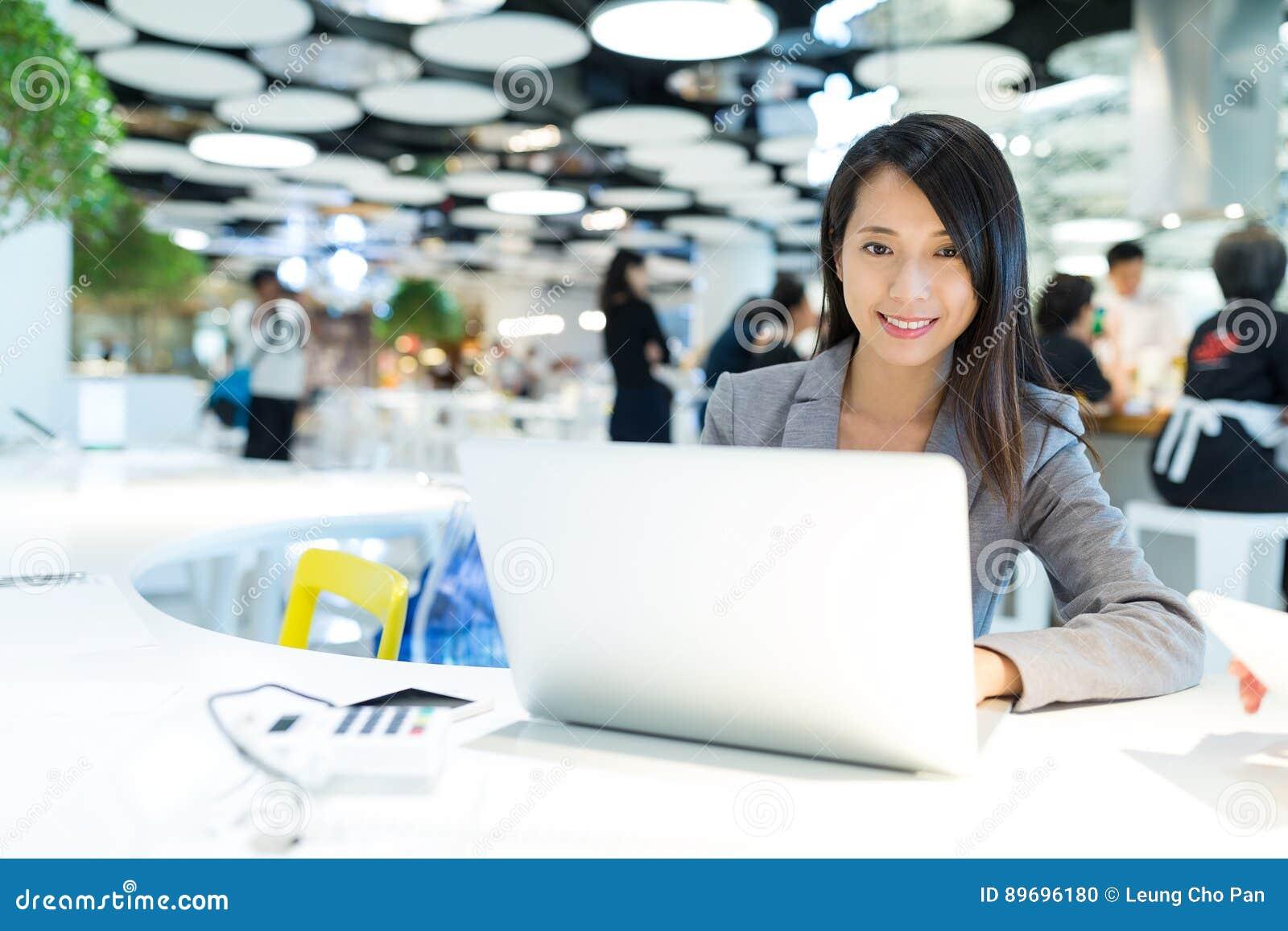 研究便携式计算机的女商人在共同工作的地方