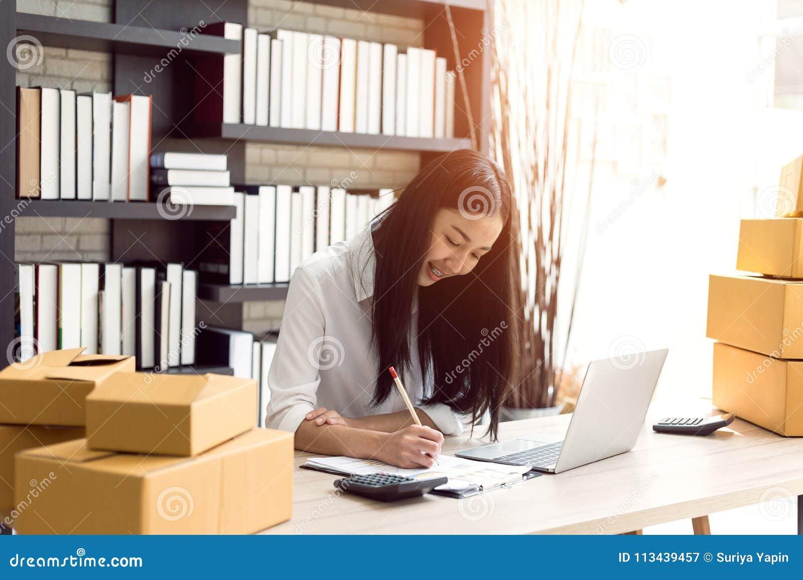 研究便携式计算机的美丽的亚裔少妇
