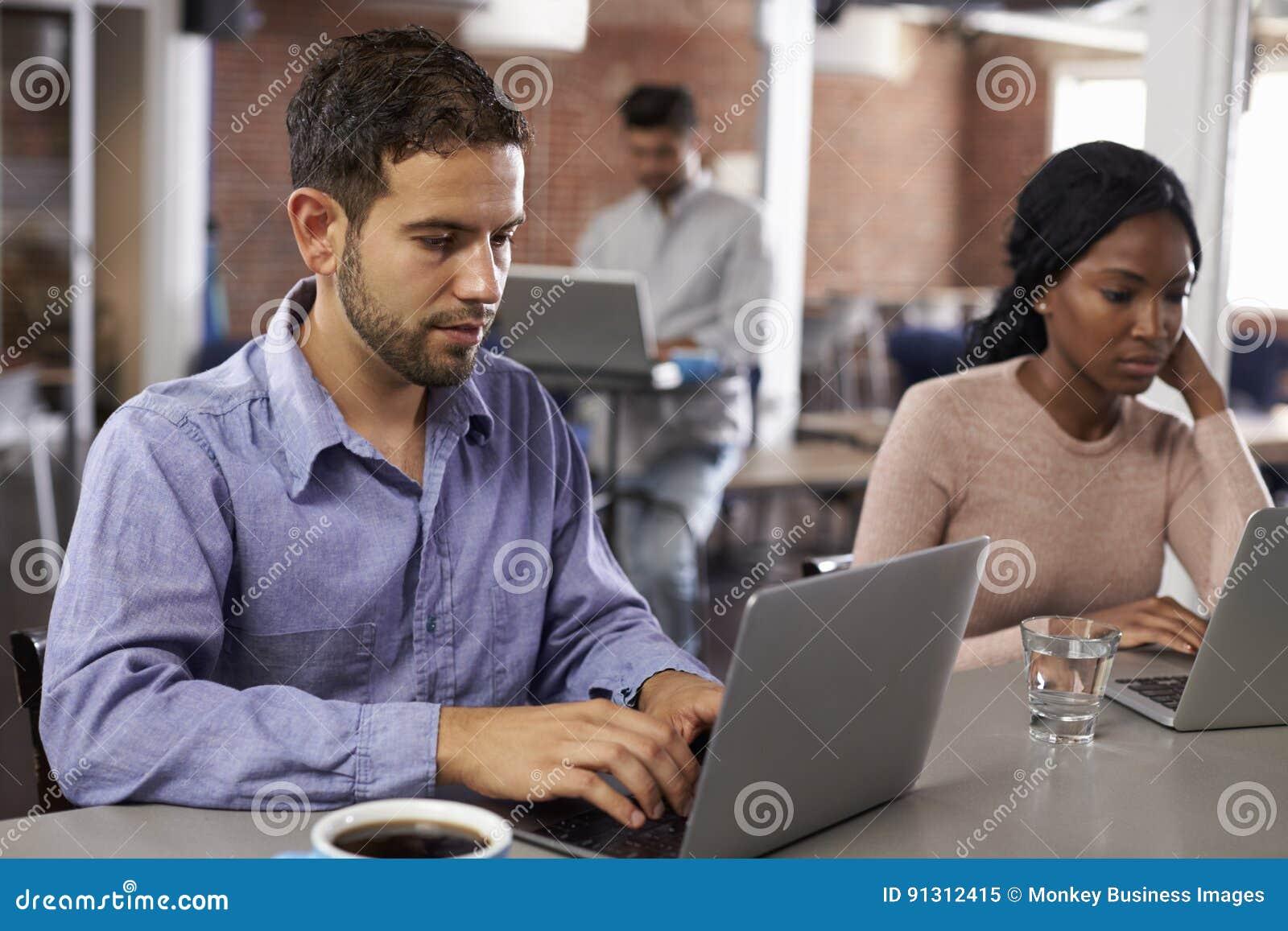 研究在办公室咖啡馆的膝上型计算机的买卖人