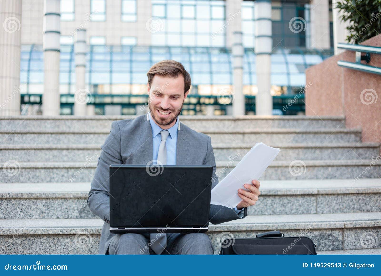 研究在办公楼前面的一台膝上型计算机的成功的年轻商人,检查纸报告