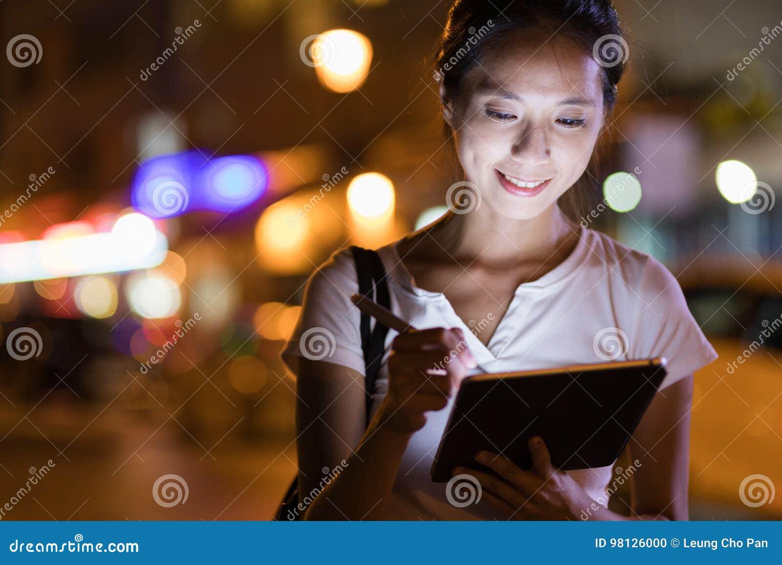 研究数字式片剂计算机的妇女在晚上