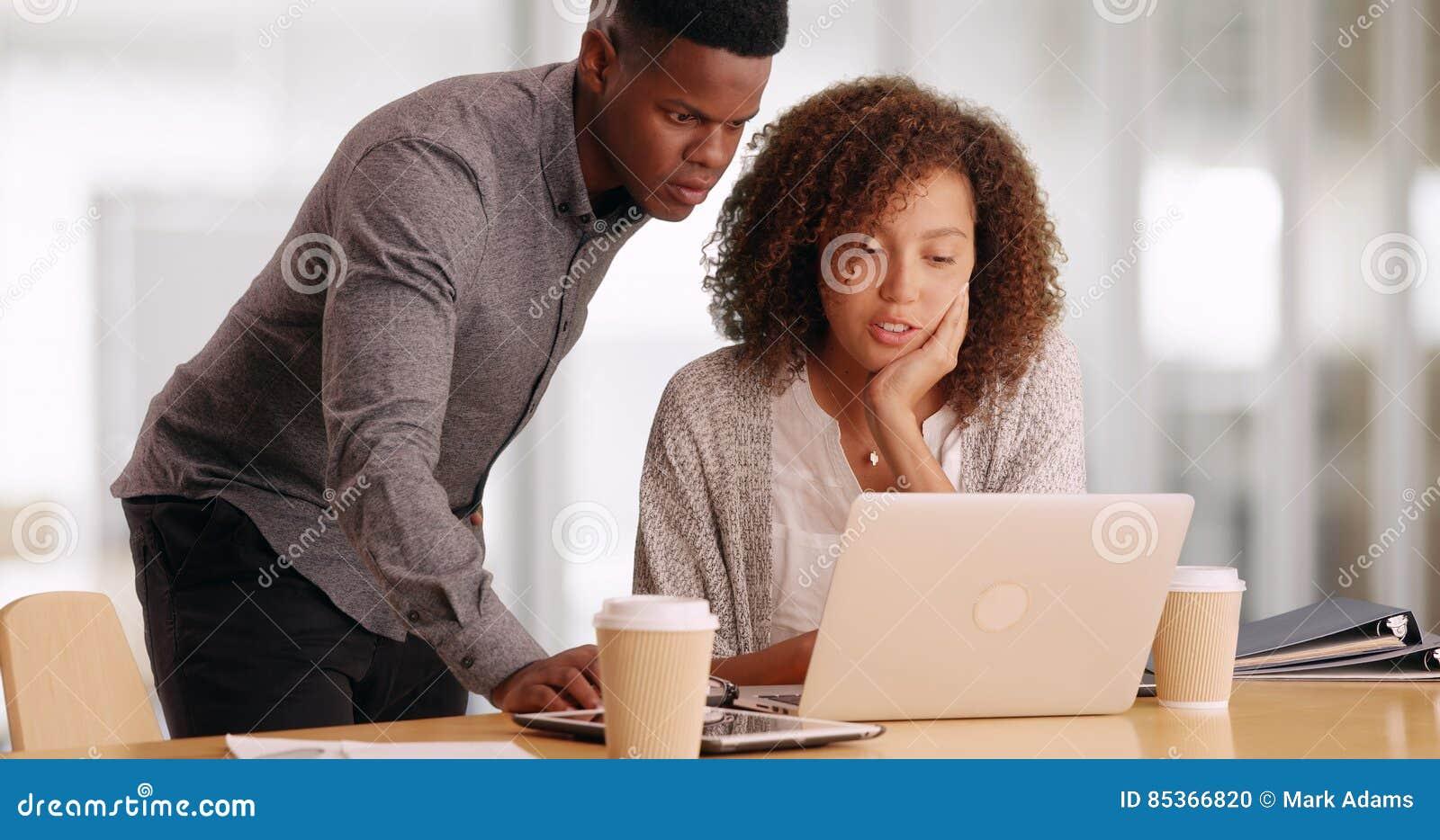 研究膝上型计算机的两个黑人商人,当喝咖啡在办公室时