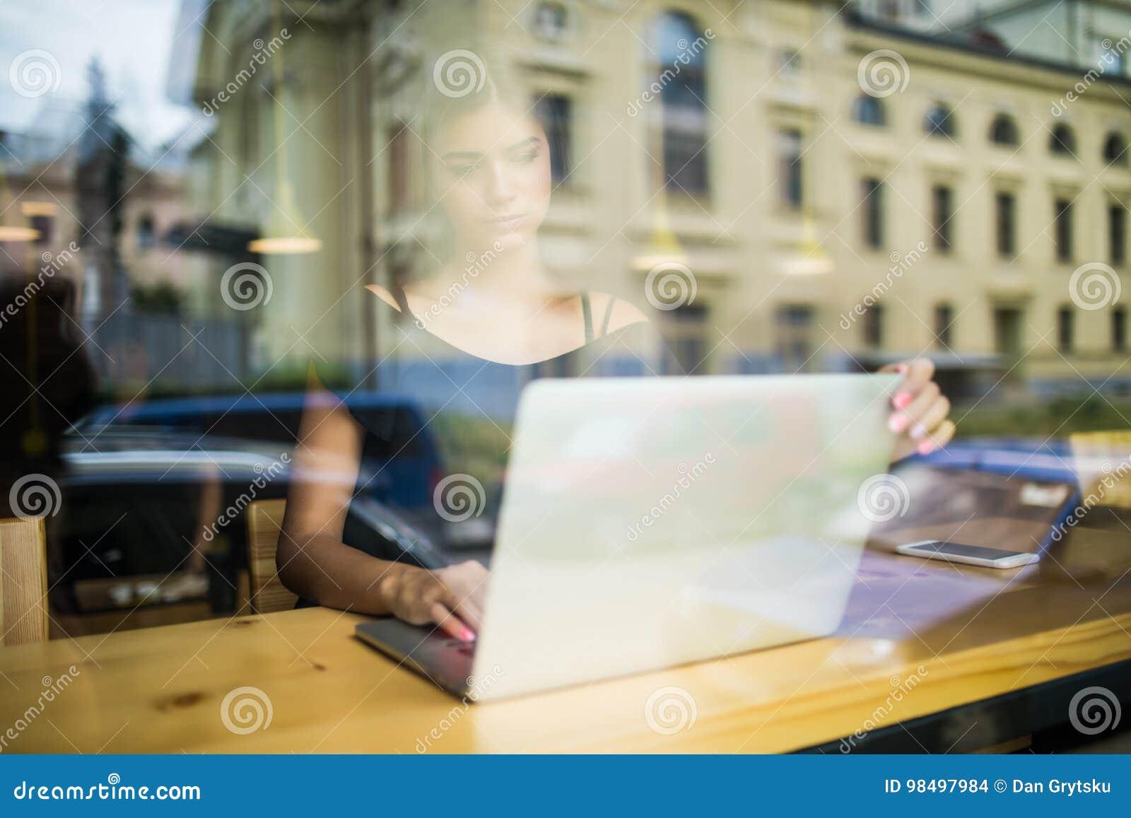 研究计算机的妇女在咖啡馆,当神色通过玻璃窗时