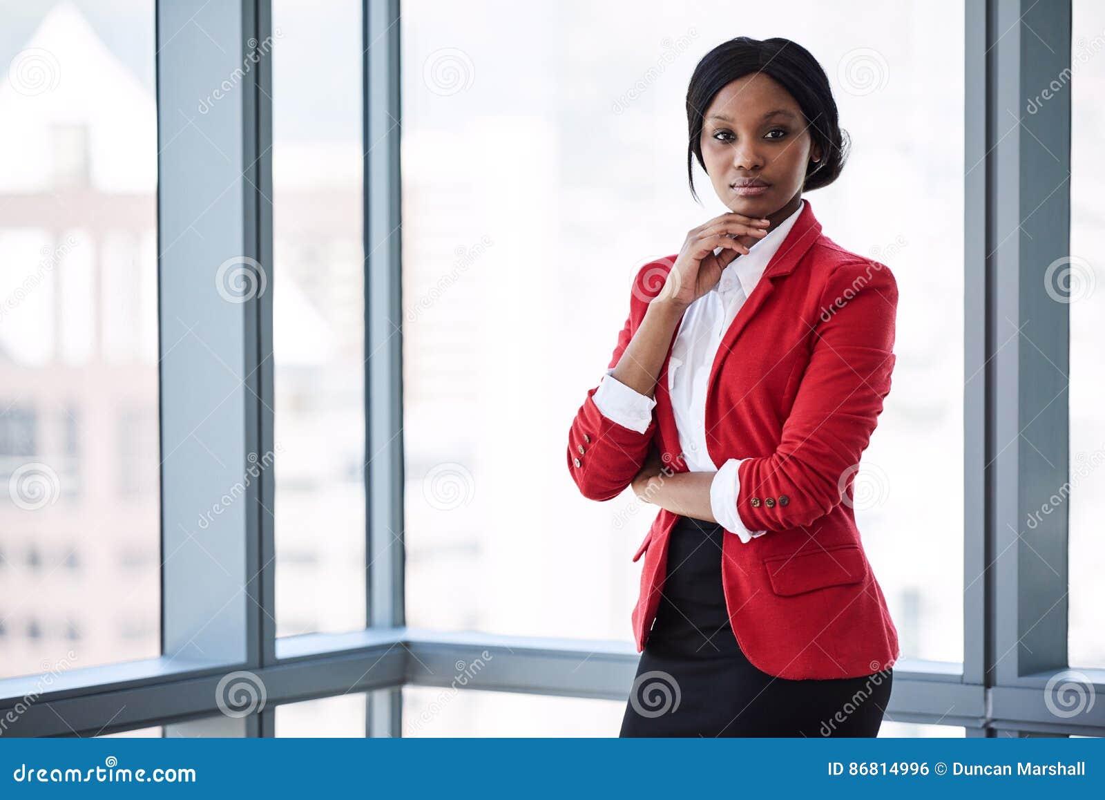 确信地调查照相机的非洲女实业家,当穿红色燃烧物时
