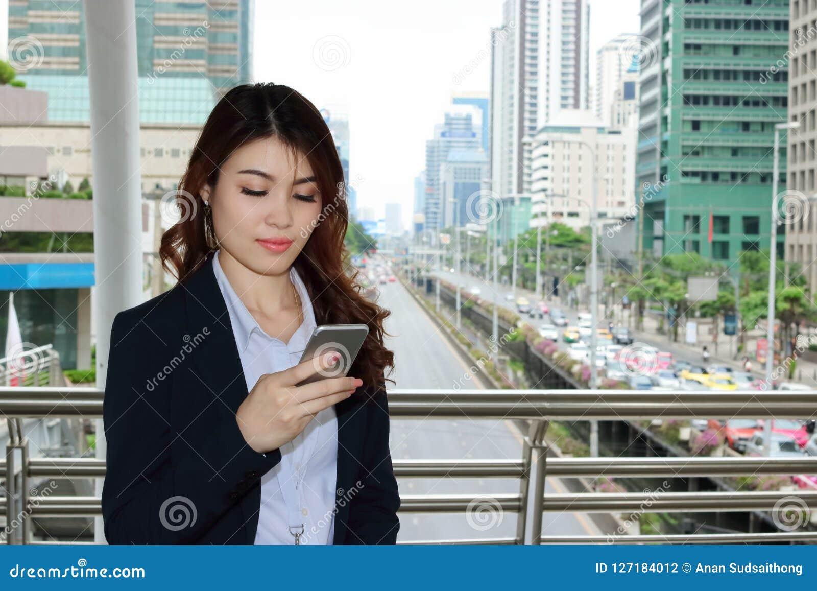 确信的年轻亚裔女商人在她的手上的注视着流动巧妙的电话都市大厦城市背景