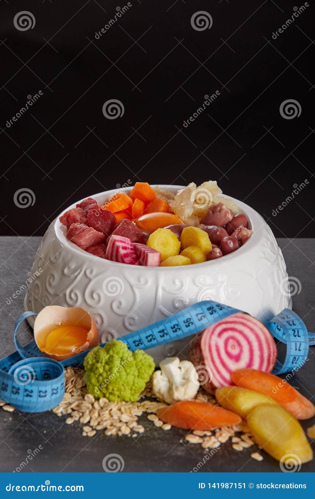 碗barf反对黑背景的食物混合