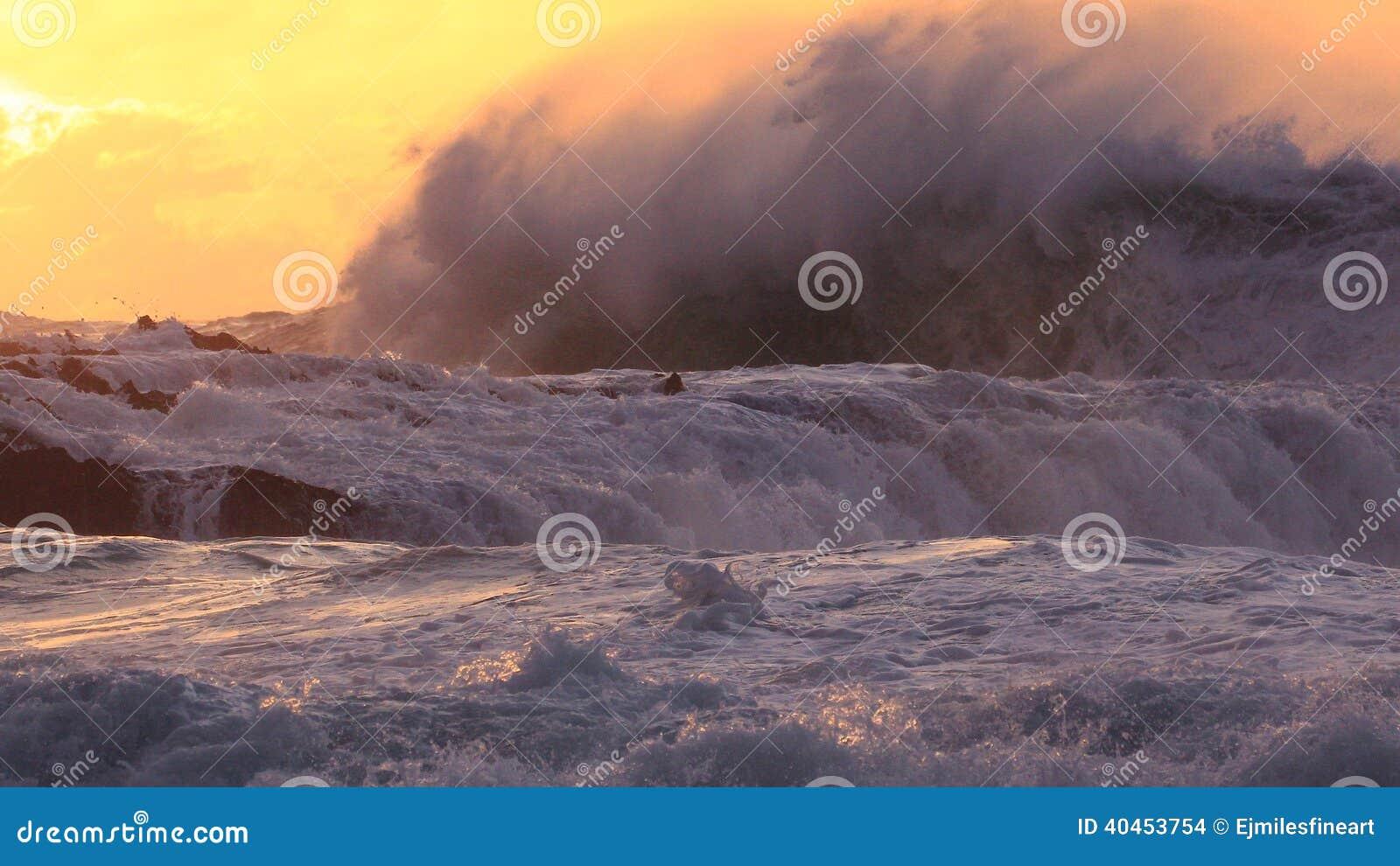 碰撞在岩石的巨大的海洋海浪在日落